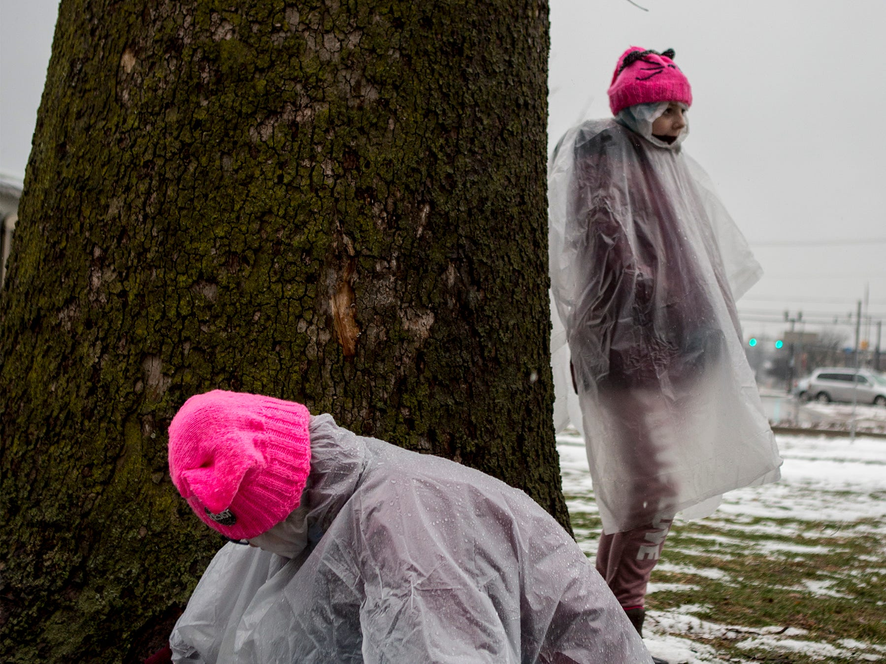 Miranda Gets of Zanesville leans against a tree listening to speakers at the Women's March in Newark while keeping an eye on her sister, who was looking for worms at the base of the tree.