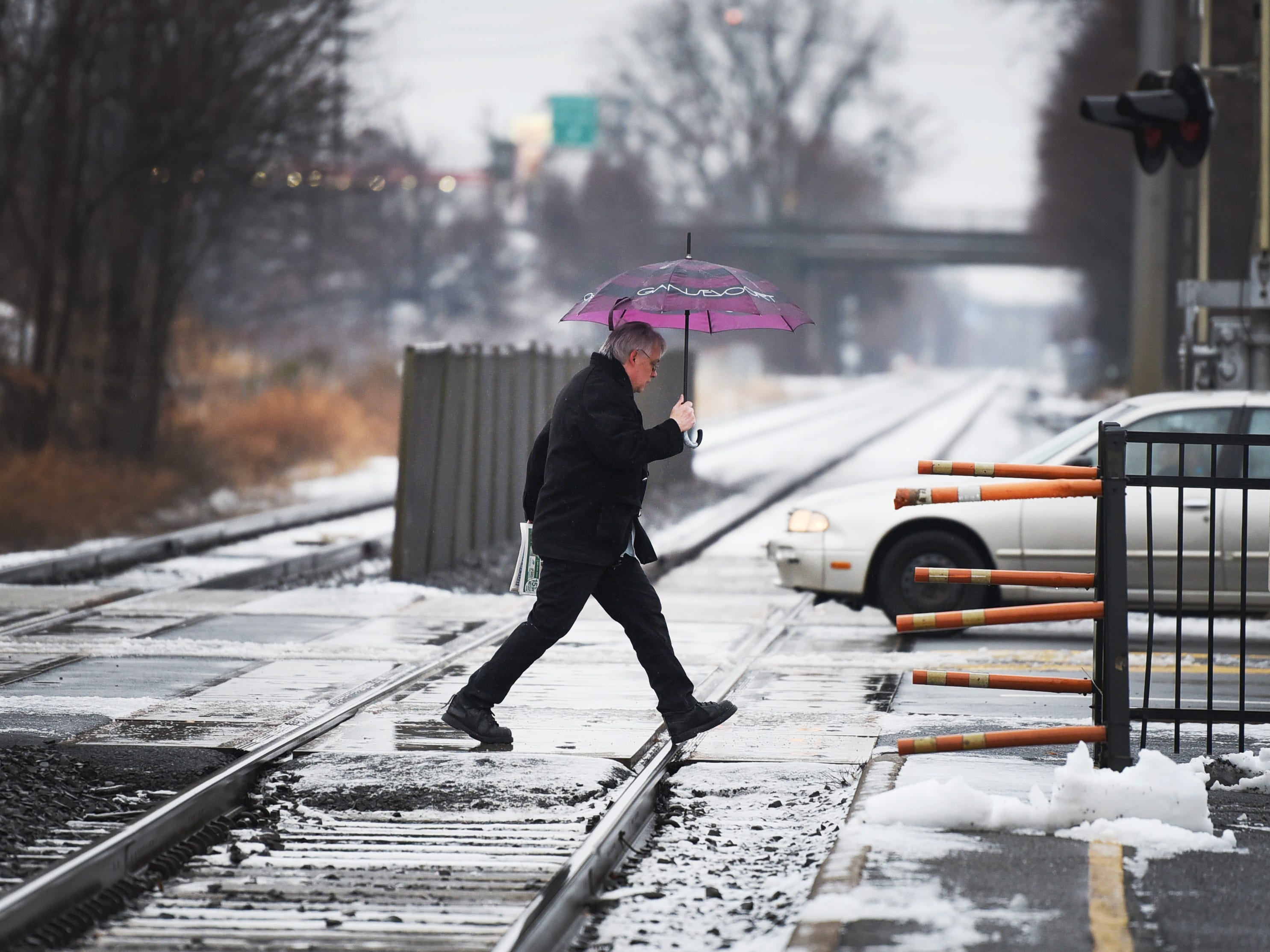 A commuter crosses over the railroad tracks at Radburn station on Sunday morning in Fair Lawn, NJ on 01/20/19.