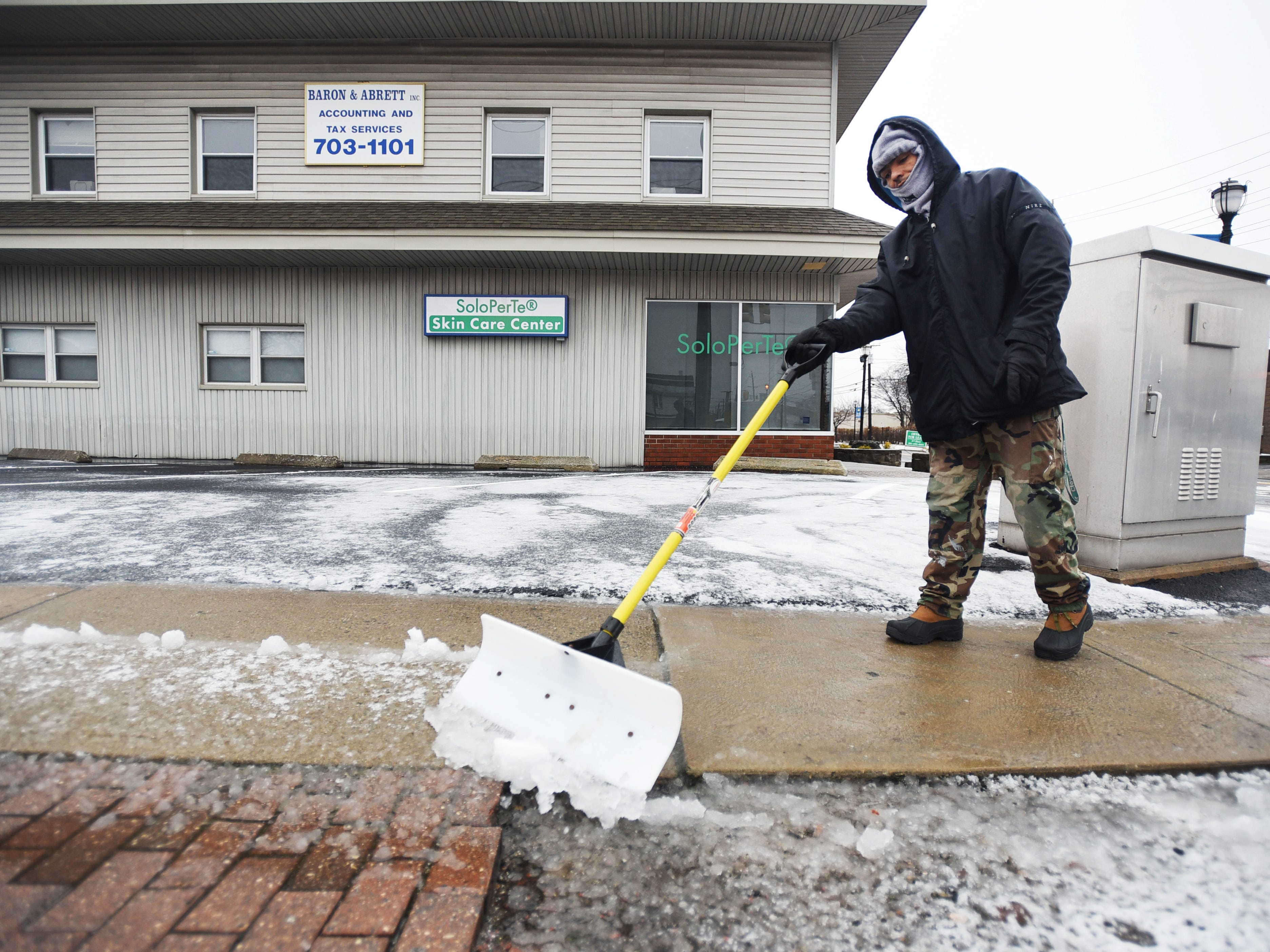 Jose Bid, a contract worker removes the snow in front of a store along Fair Lawn Avenue on Sunday morning in Fair Lawn, NJ on 01/20/19.