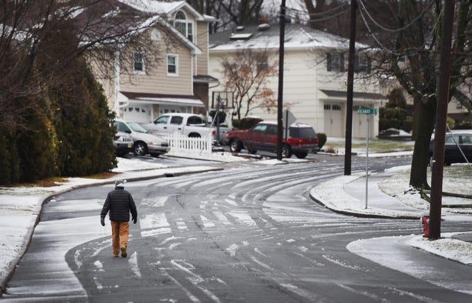 A man walks along a slushy road in Fair Lawn on Sunday morning in Fair Lawn, NJ on 01/20/19.