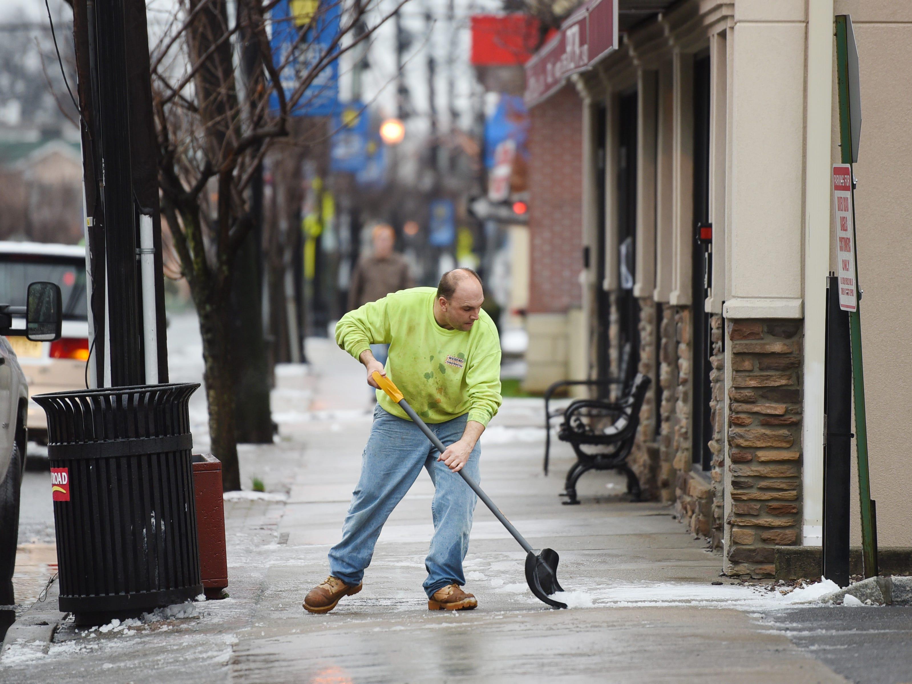 Robert Weidener removes slushy snow from the sidewalk along Fair Lawn Avenue on Sunday morning in Fair Lawn, NJ on 01/20/19.