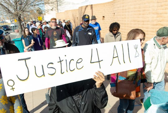 Marchers carry signs on Sunday, Jan. 20, 2019, during the Doña Ana County NAACP annual MLK March in downtown Las Cruces.