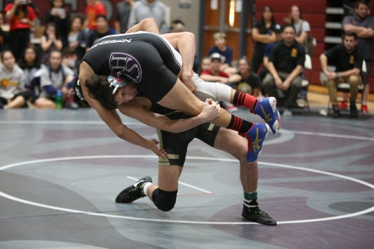 Palm Desert's Troy Mantanona lifts his opponent Isaac Chaidez of Shadow Hills during his championship victory at the DEL wrestling finals on Saturday.