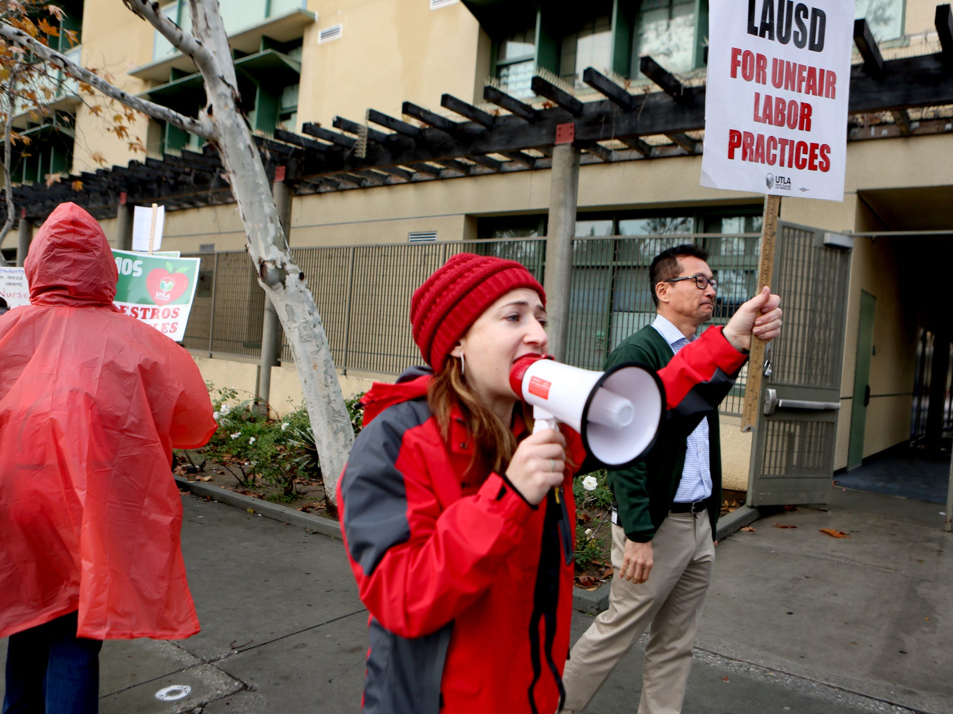 Charles H. Kim Elementary School resource teacher Miriam Feigelstock uses a megaphone to ask parents and students not to cross the picket line as principal Jonathan Paek, right, welcomes students during the third day of the United Teachers Los Angeles strike in Los Angeles on Wednesday, January 16, 2019.