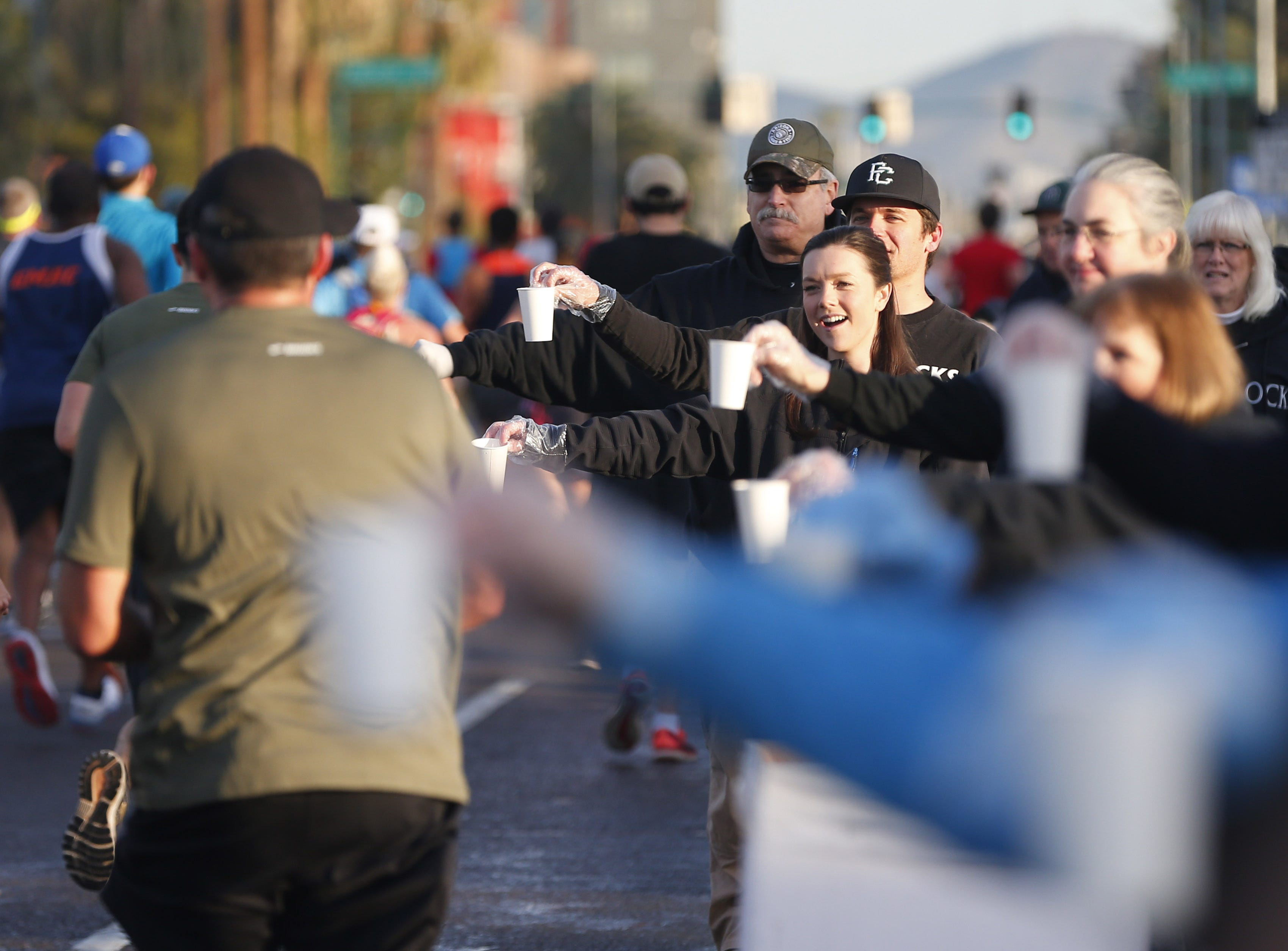 Volunteers offer water to runners on 7th Ave. during the Rock 'n' Roll Marathon in Phoenix, Jan. 20, 2019.