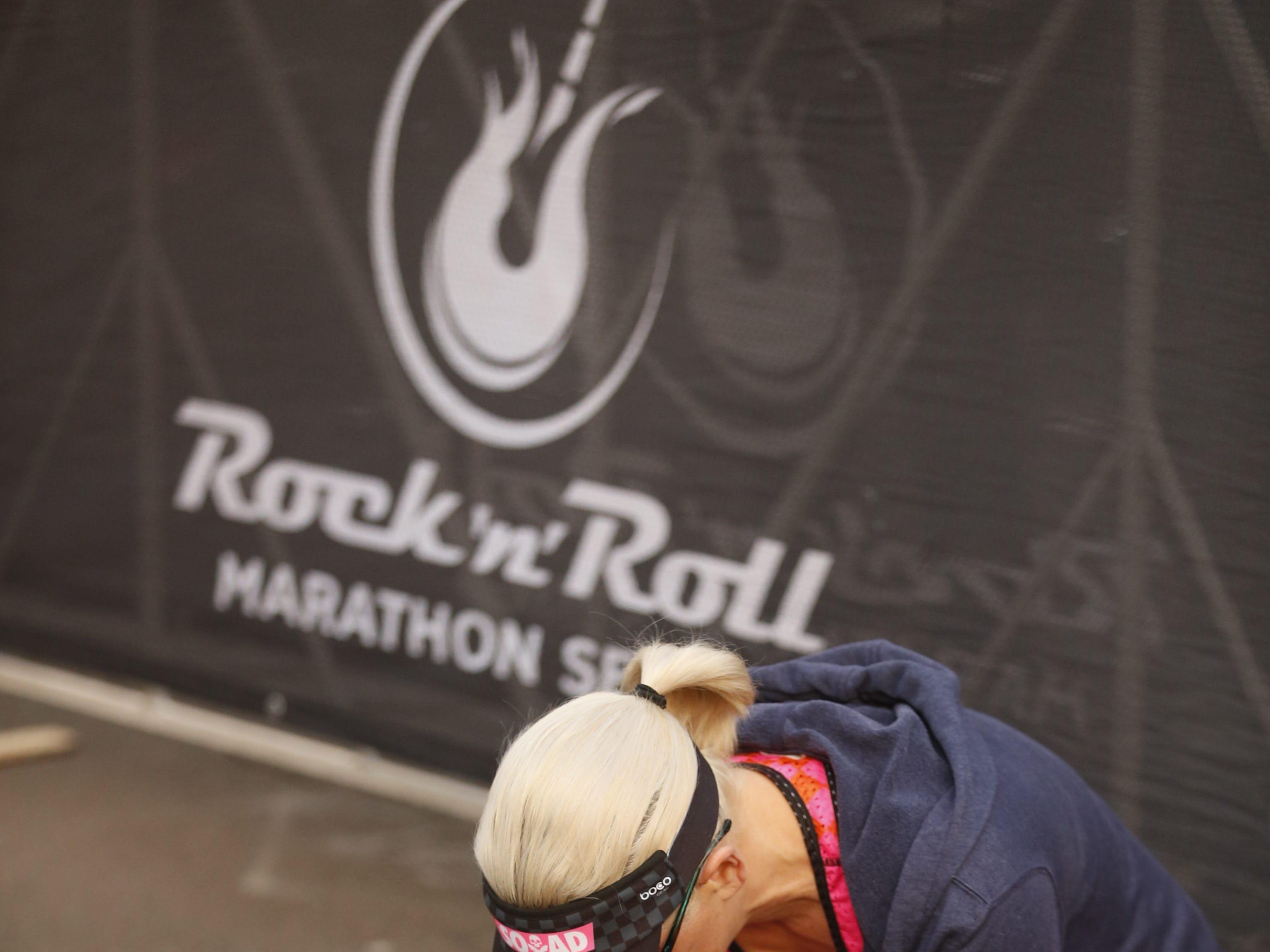 Sen. Kyrsten Sinema ties her shoes before the Rock 'N' Roll half-marathon in Temp. on Jan 20, 2019.