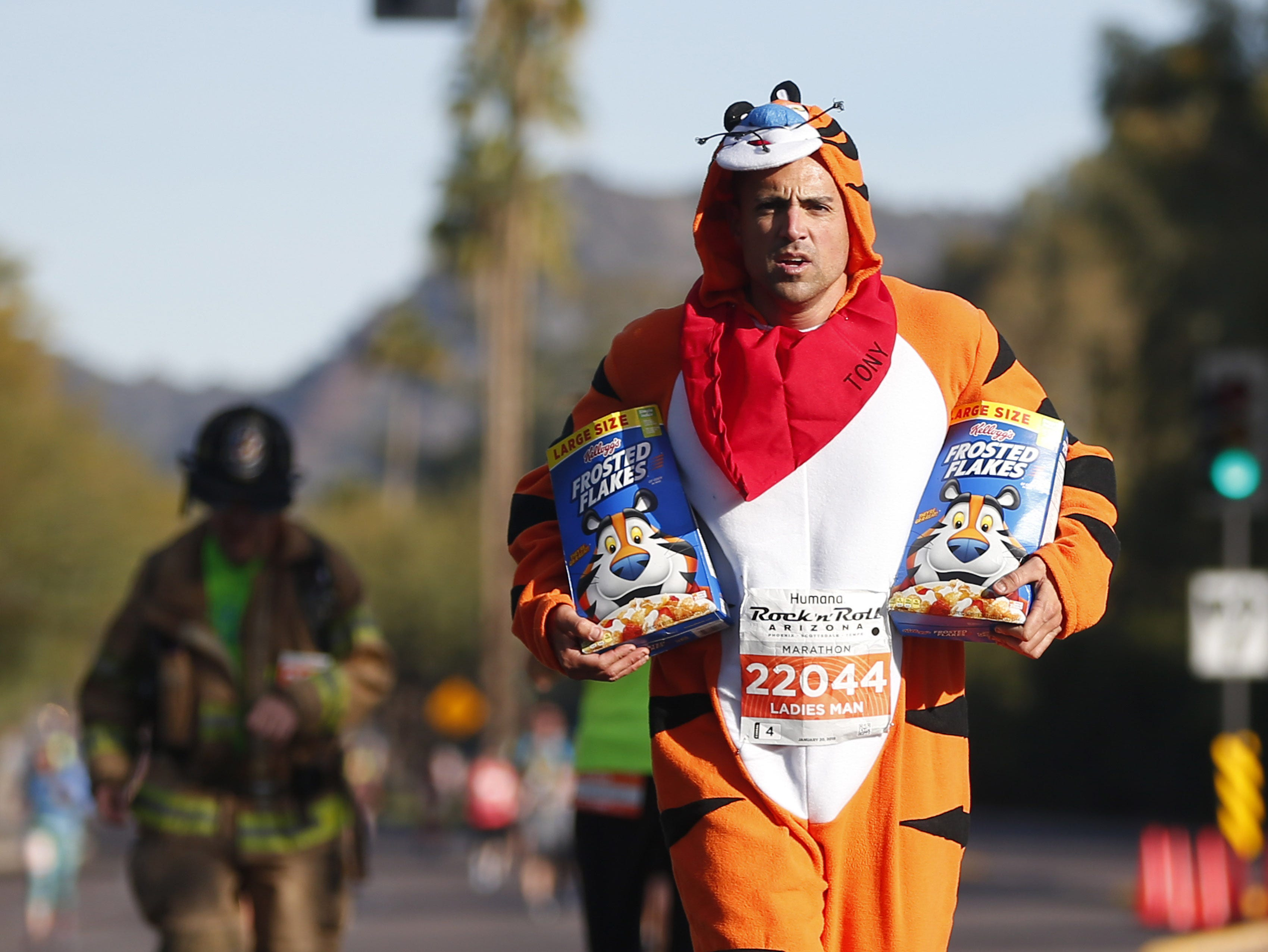 Sam Goldberg runs with cereal on 24th St. at the Rock 'N' Roll Marathon in Phoenix on Jan. 20, 2019.