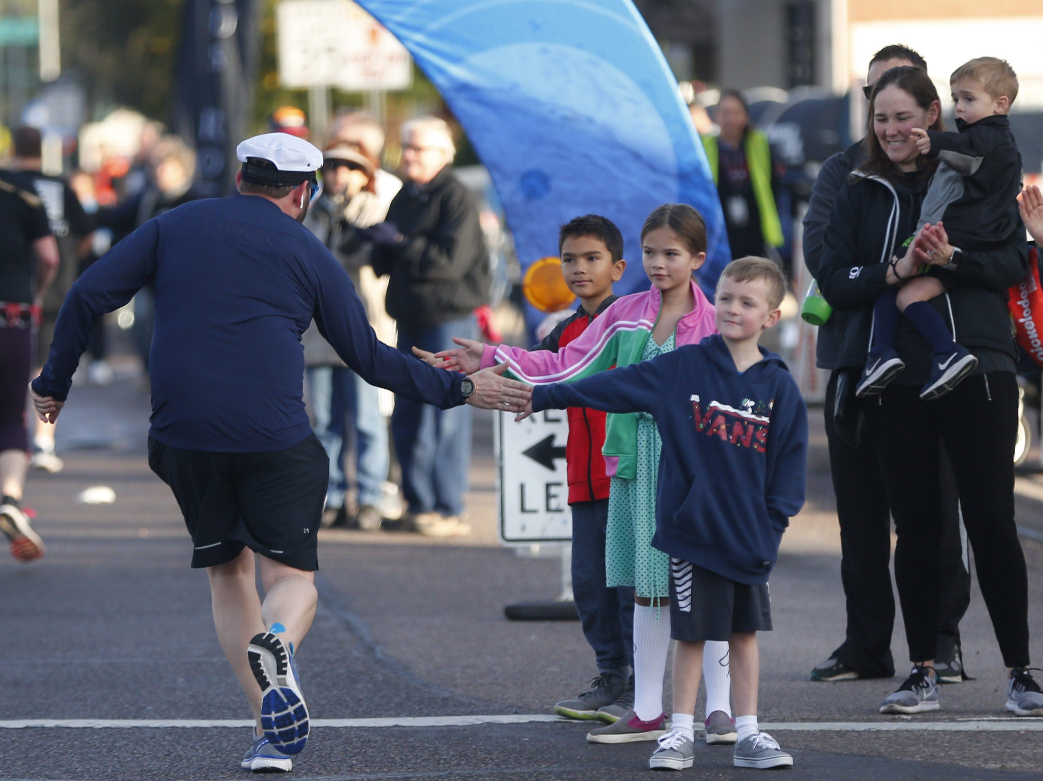Spectators greet runners on 7th Ave. during the Rock 'n' Roll Marathon in Phoenix, Jan. 20, 2019.