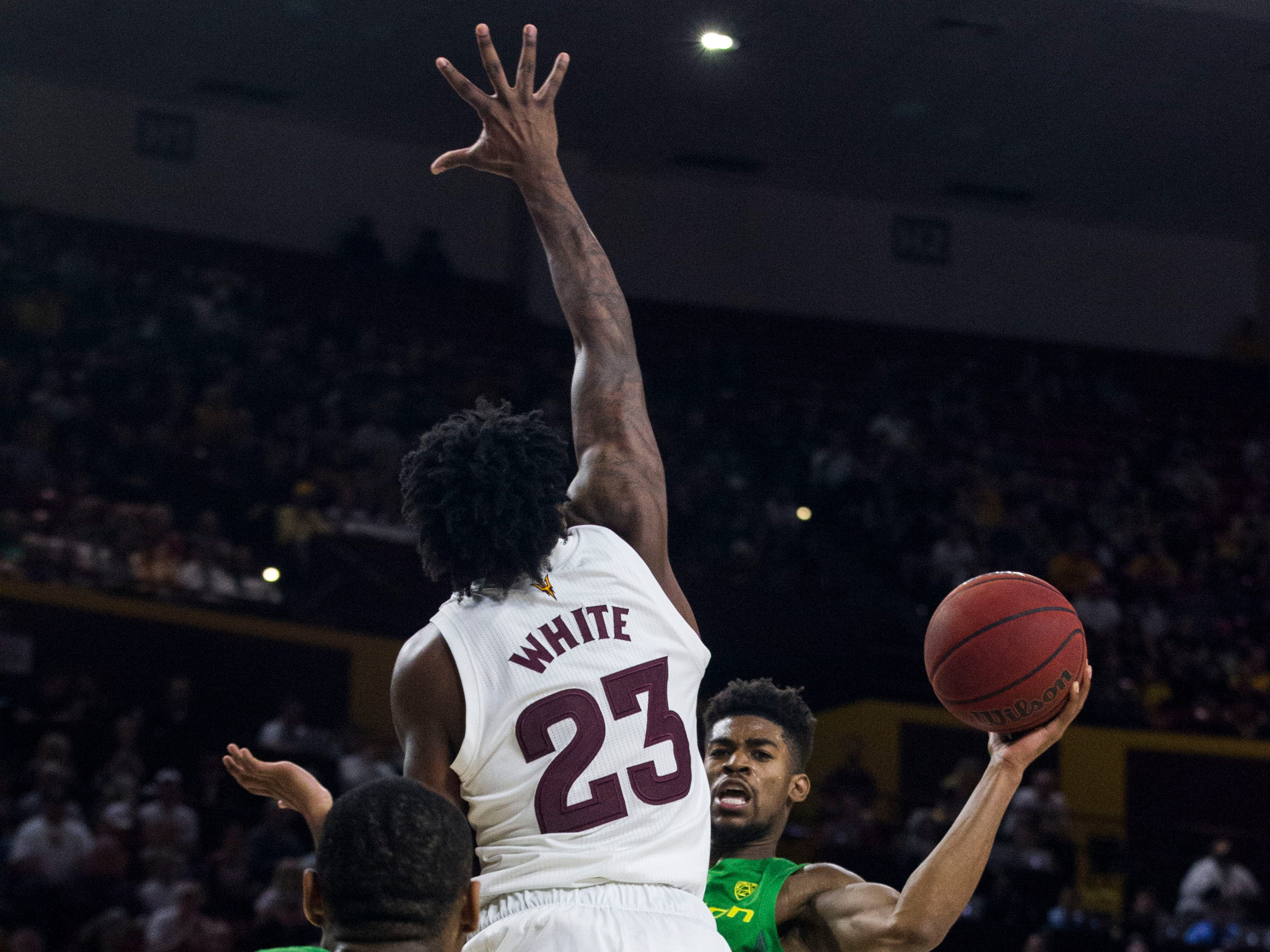 Oregon's Victor Bailey Jr. (10) looks to pass around Arizona State's Romello White (23) to Francis Okoro (33) during the first half, Saturday, Jan. 19, 2019, in Tempe, Ariz. (AP Photo/Darryl Webb)