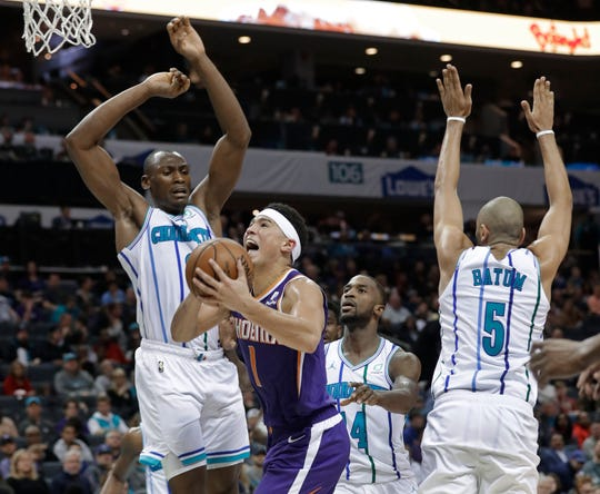 Suns' Devin Booker (1) drives between Hornets' Nicolas Batum (5) and Bismack Biyombo during the second half of Saturday's game.