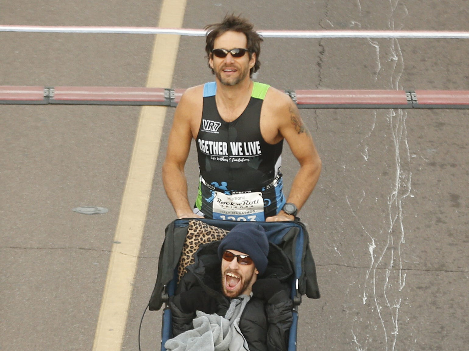 Matthew Reines pushes Patrick Canez at the start of the Rock 'N' Roll half-marathon in Tempe on Jan. 20, 2019.