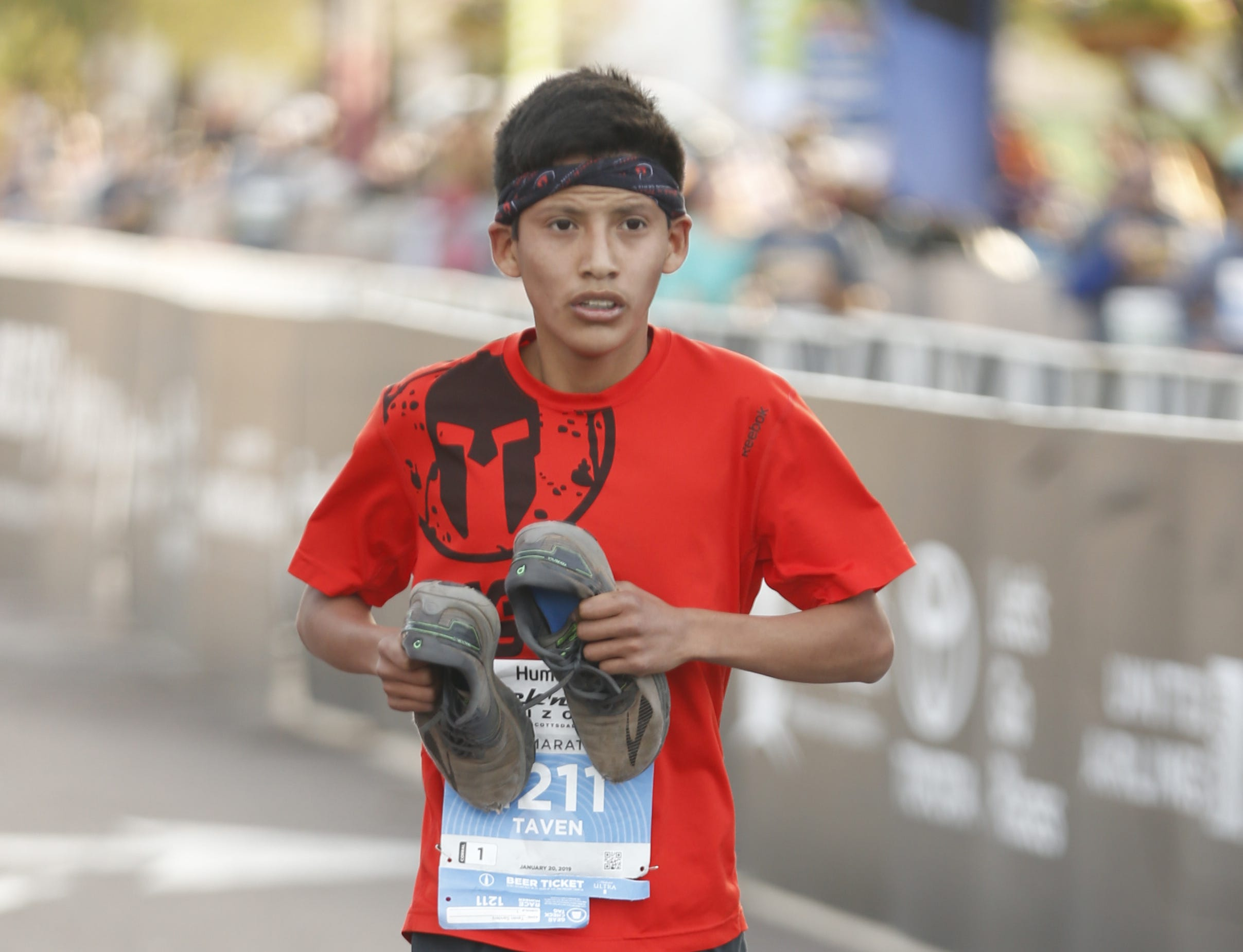 Taven Sanders runs across the finish line holding his shoes during the Rock 'N' Roll half-marathon in Tempe on Jan. 20, 2019.