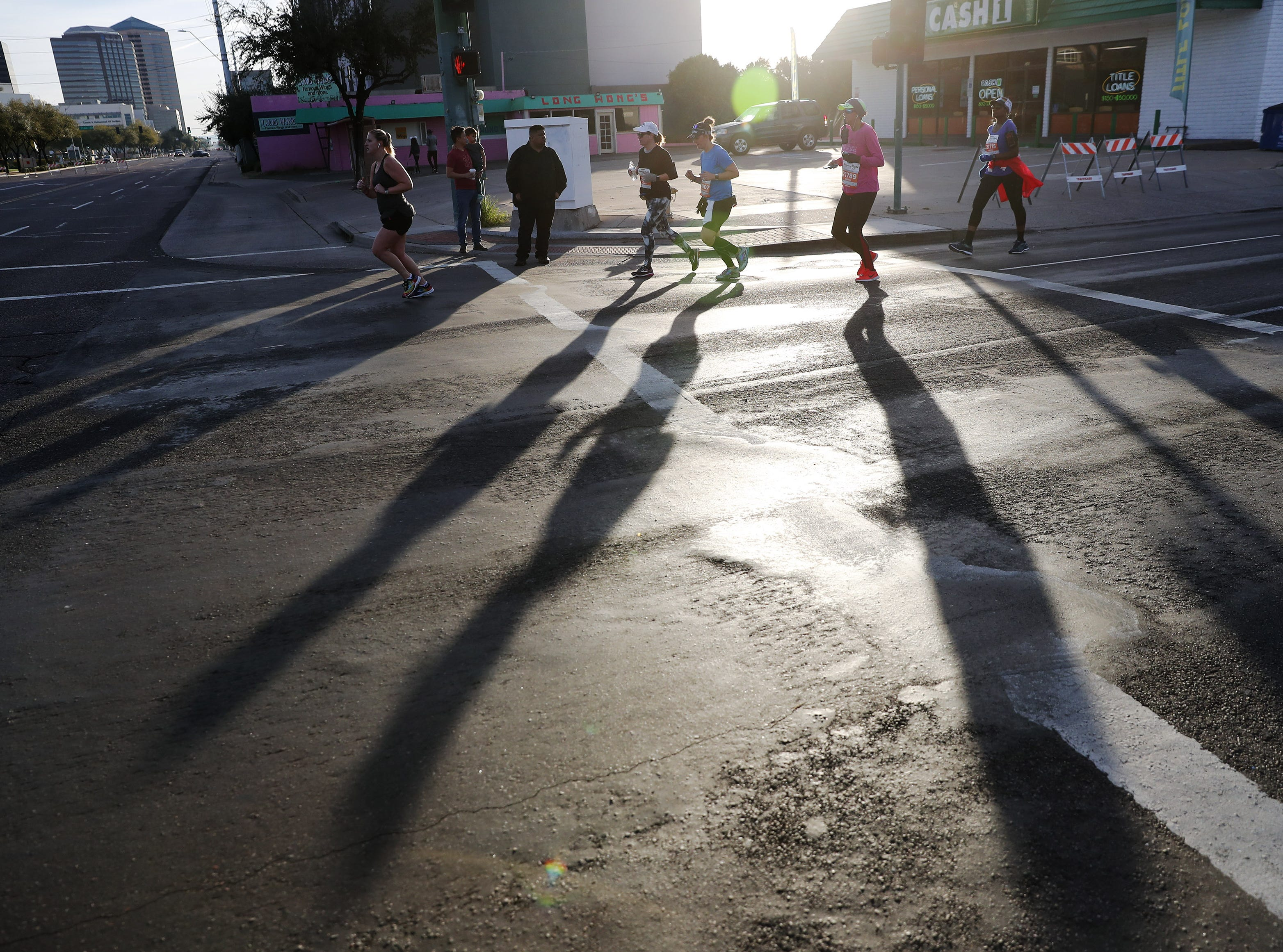 Runners cast shadows on 7th Ave. during the Rock 'n' Roll Marathon in Phoenix Jan. 20, 2019.