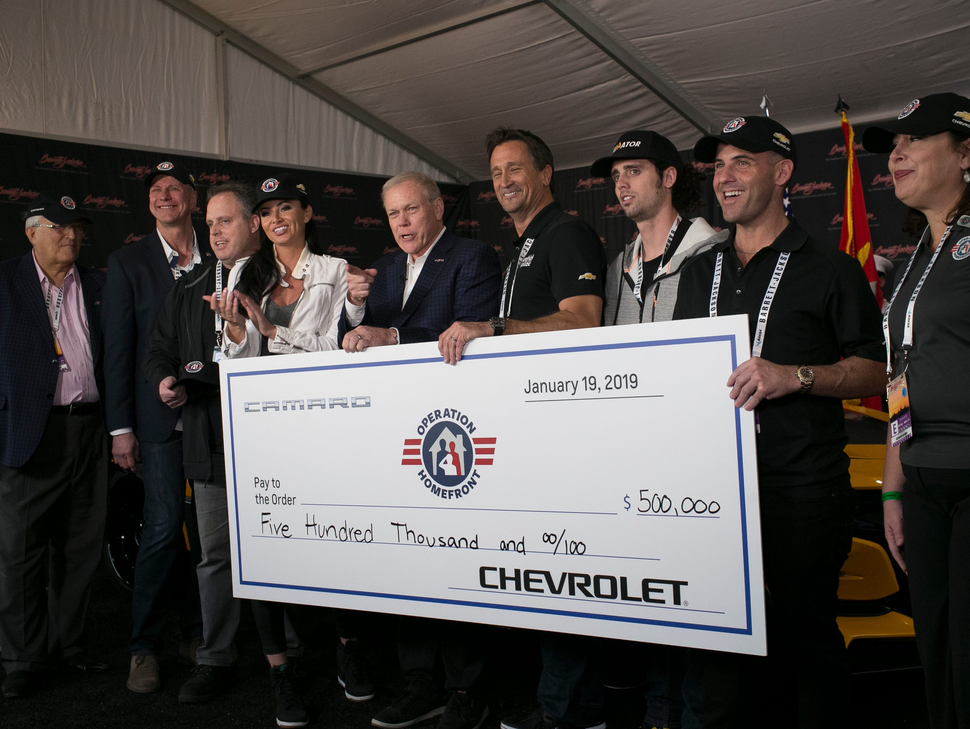 The $500,000 check given to Operation Homefront for the purchase of Four original Bumblebee Camaros from the Transformers film franchise bought by Rick Hendrick, owner of NASCAR team Hendrick Motorsports, is held for a photo-op with Craig Jackson, chairman and CEO of Barrett-Jackson (center), at WestWorld on Jan. 19, 2019, in Scottsdale.