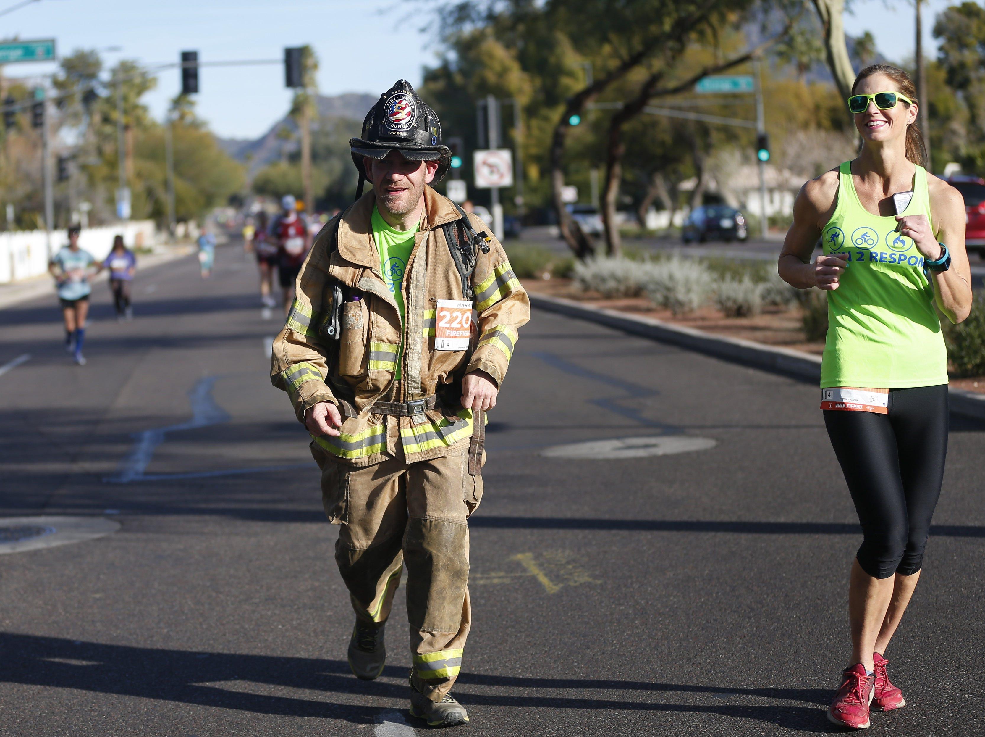 Steve Bender runs in firefighting gear on 24th St. at the Rock 'N' Roll Marathon in Phoenix Jan. 20, 2019.