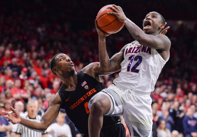 Jan 19, 2019; Tucson, AZ, USA; Arizona Wildcats guard Justin Coleman (12) attempts to shoot as Oregon State Beavers forward Alfred Hollins (4) defends during the second half at McKale Center. Mandatory Credit: Casey Sapio-USA TODAY Sports