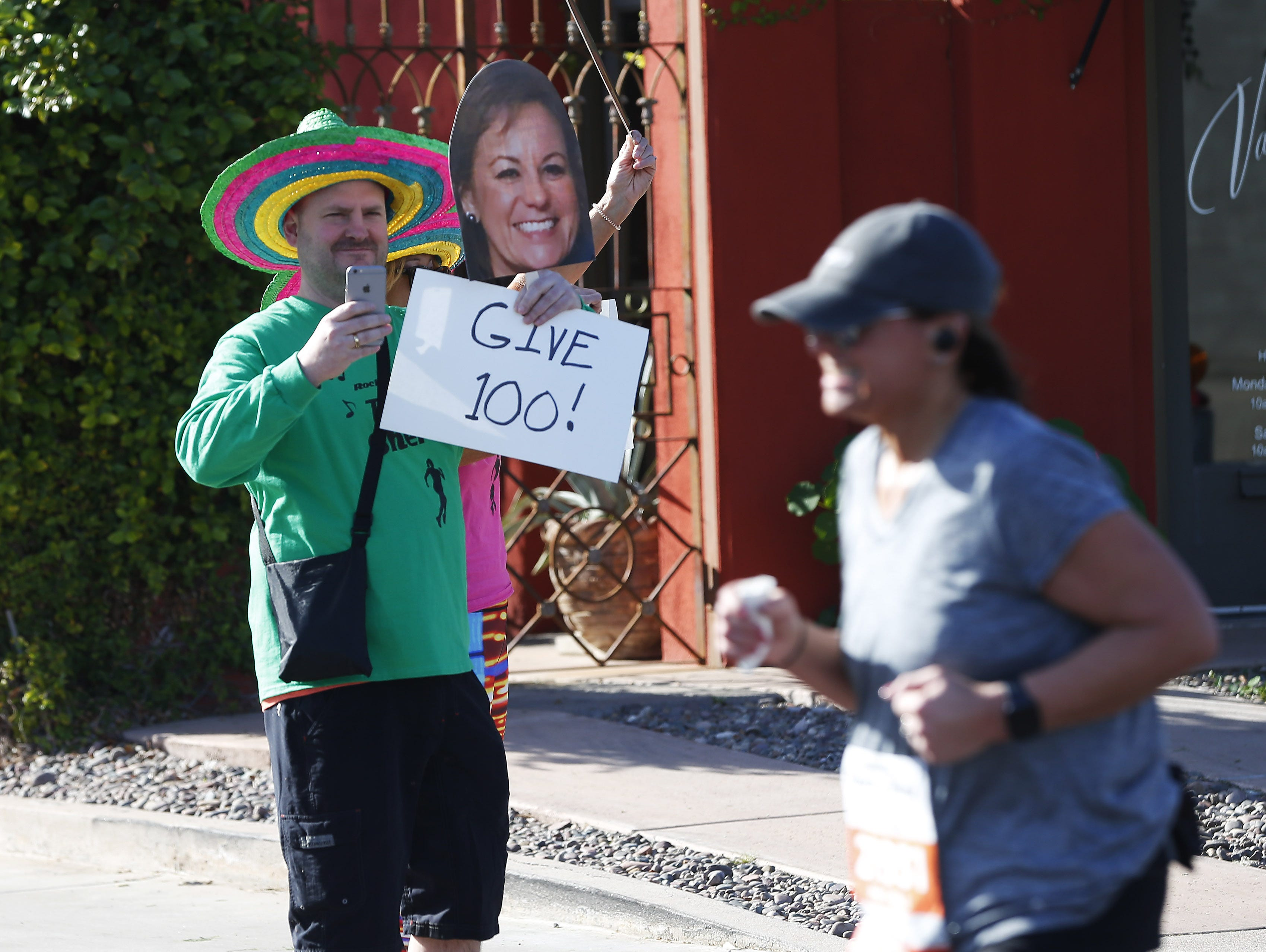 Bryce Nelson supports his wife, Shere Lenz, running on 1st Ave. during the Rock 'N' Roll Marathon in Scottsdale on Jan. 20, 2019.