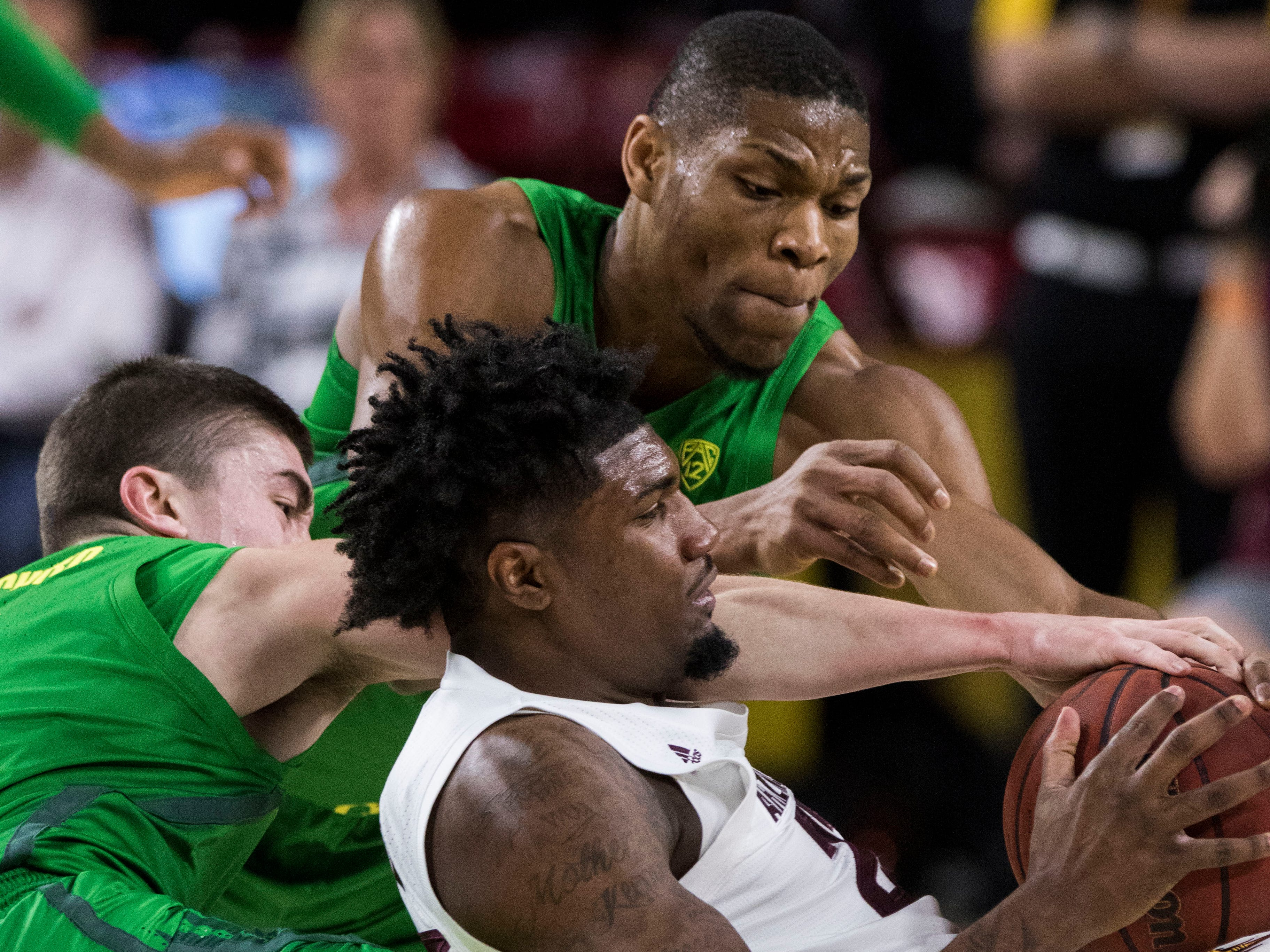 Arizona State's Romello White (23) controls the ball as he battles against Oregon's Payton Pritchard (3) and Francis Okoro (33) during the first half, Saturday, Jan. 19, 2019, in Tempe, Ariz. (AP Photo/Darryl Webb)