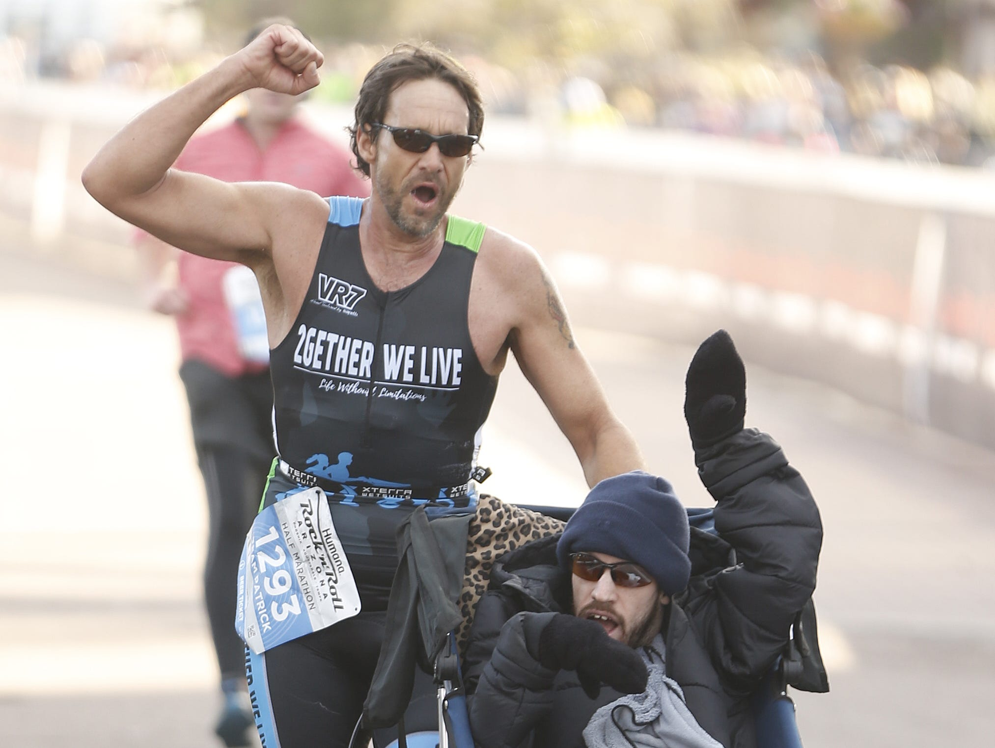 Matthew Reines pushes Patrick Canez across the finish line during the Rock 'n' Roll half-marathon in Tempe on Jan. 20, 2019.