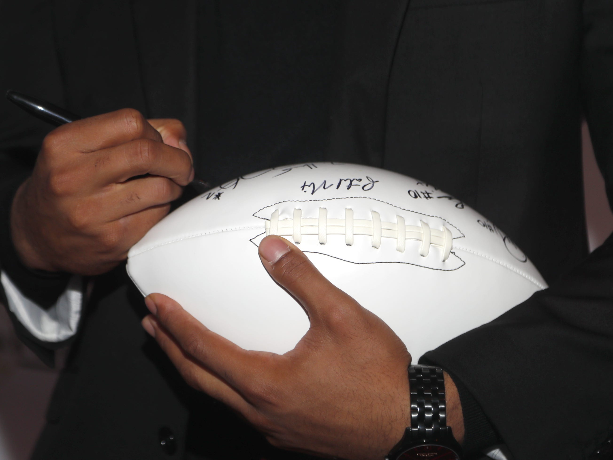 Oklahoma quarterback Jalen Hurts signs a football before the National Quarterback Club Awards Dinner & Hall of Fame Induction Ceremony The Scottsdale Resort at McCormick Ranch in Scottsdale, Ariz. on January 19, 2019.