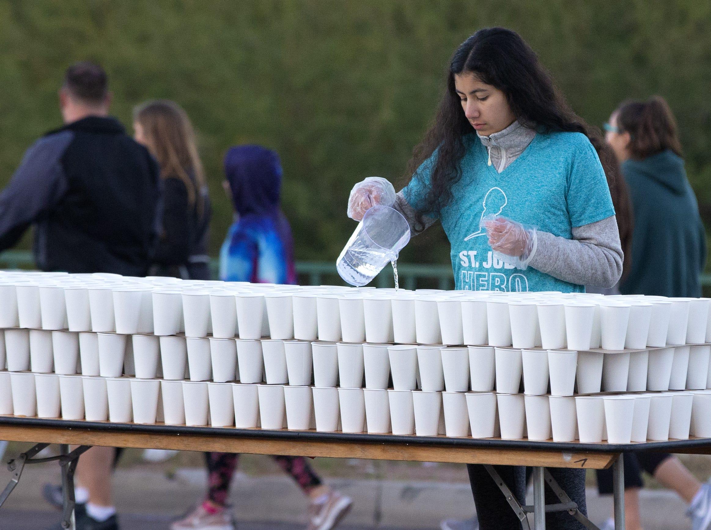 St. Jude volunteer Rachel Etebari pours water for the runners during the Humana Rock 'N' Roll half marathon on Jan. 20, 2019.