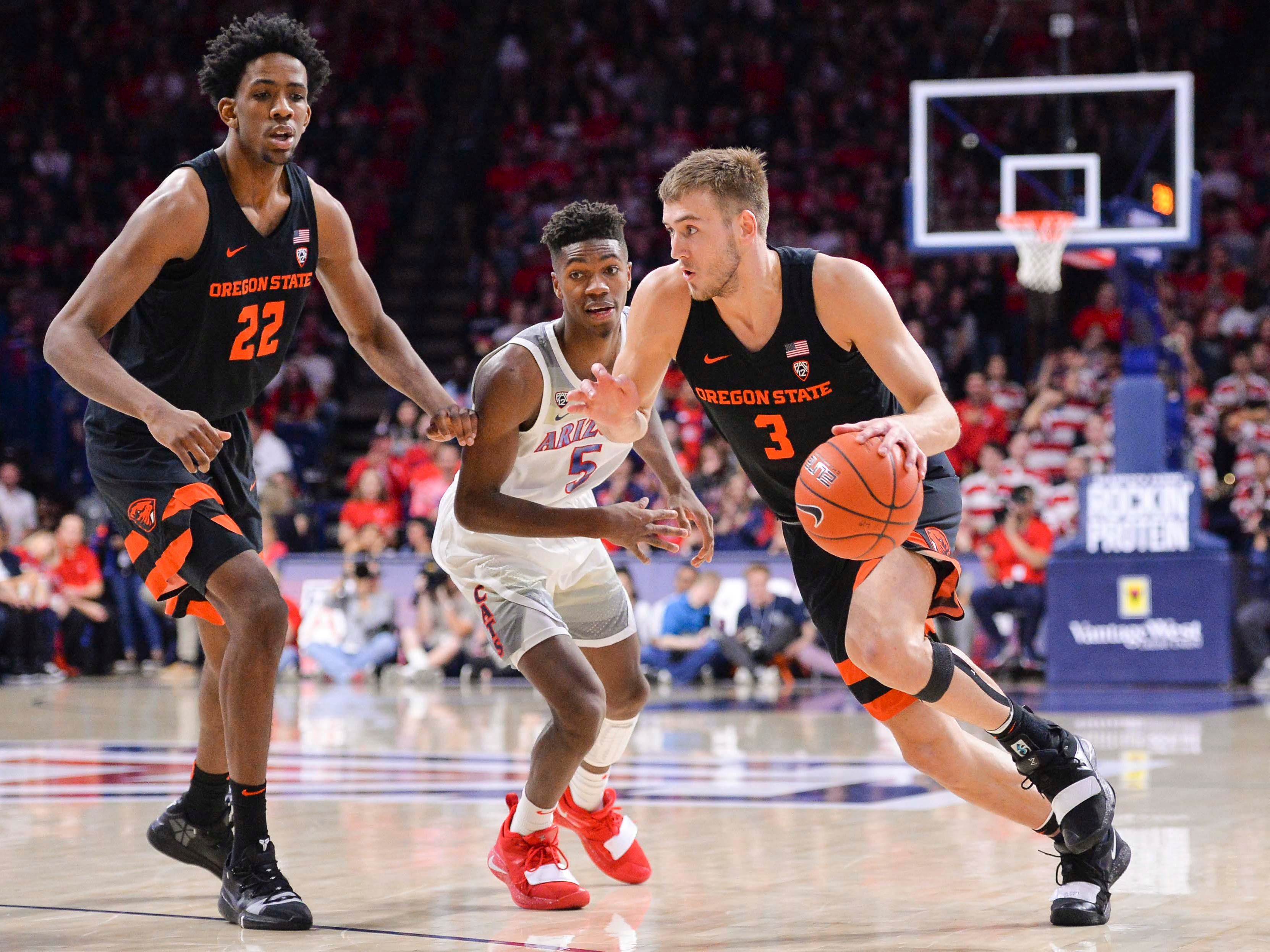Jan 19, 2019; Tucson, AZ, USA; Oregon State Beavers forward Tres Tinkle (3) drives past forward Warren Washington (22) and Arizona Wildcats guard Brandon Randolph (5) during the first half at McKale Center. Mandatory Credit: Casey Sapio-USA TODAY Sports
