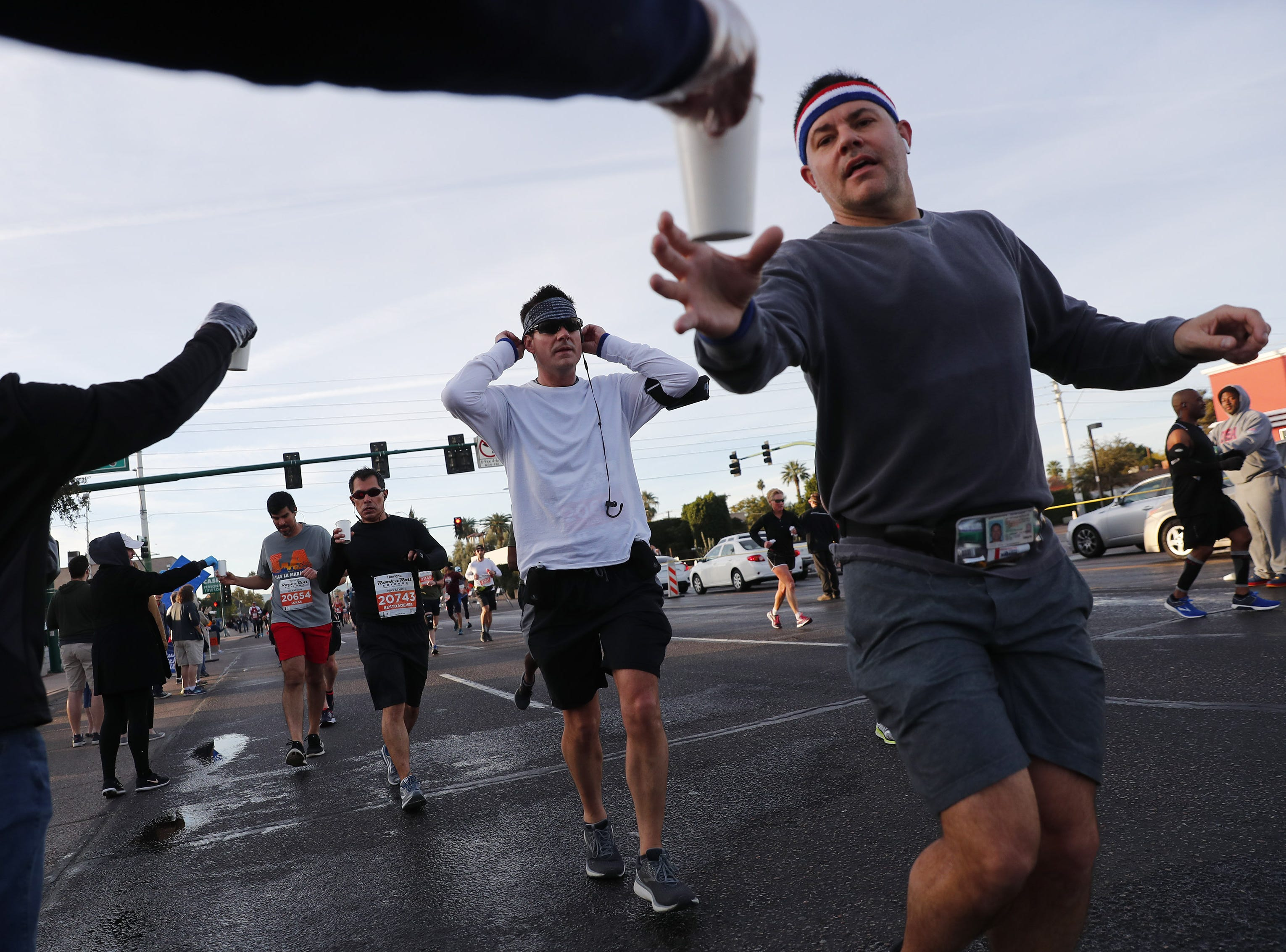 Runners grab water on 7th Ave. during the Rock 'n' Roll Marathon in Phoenix, Jan. 20, 2019.