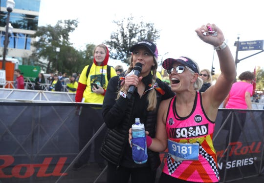 Sen. Kyrsten Sinema celebrates with emcee Ann Wessling after Sinema finished the Rock 'N' Roll half-marathon in Tempe on Jan. 20, 2019.