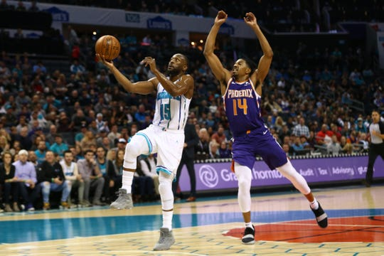 Jan 19, 2019; Charlotte, NC, USA; Charlotte Hornets guard Kemba Walker (15) goes up for a shot while Phoenix Suns guard De'Anthony Melton (14) defends in the first half at Spectrum Center. Mandatory Credit: Jeremy Brevard-USA TODAY Sports