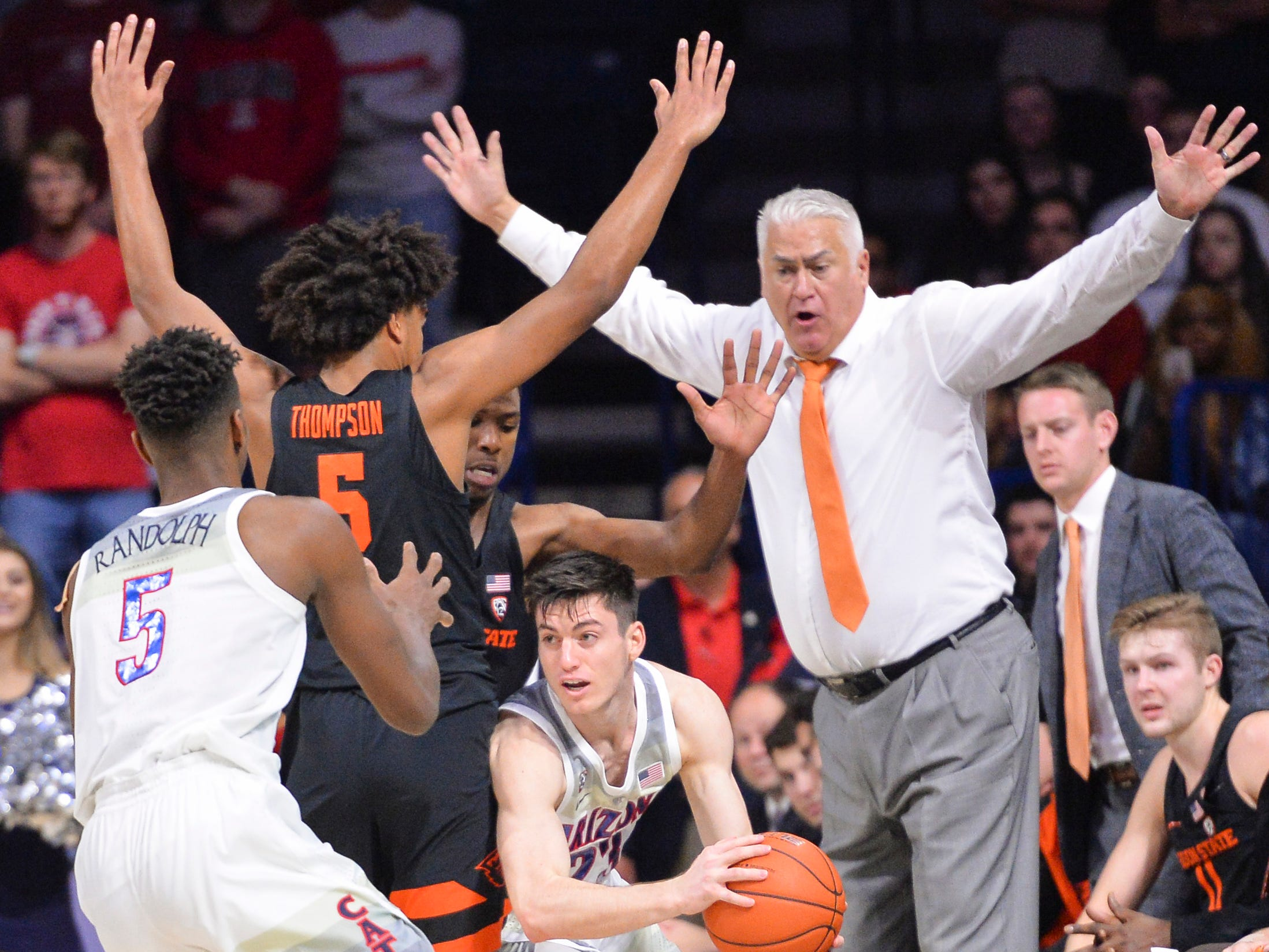Jan 19, 2019; Tucson, AZ, USA; Arizona Wildcats guard Alex Barcello (23) attempts to pass the ball as Oregon State Beavers guard Ethan Thompson (5) and head coach Wayne Tinkle (right) defend during the second half at McKale Center. Mandatory Credit: Casey Sapio-USA TODAY Sports
