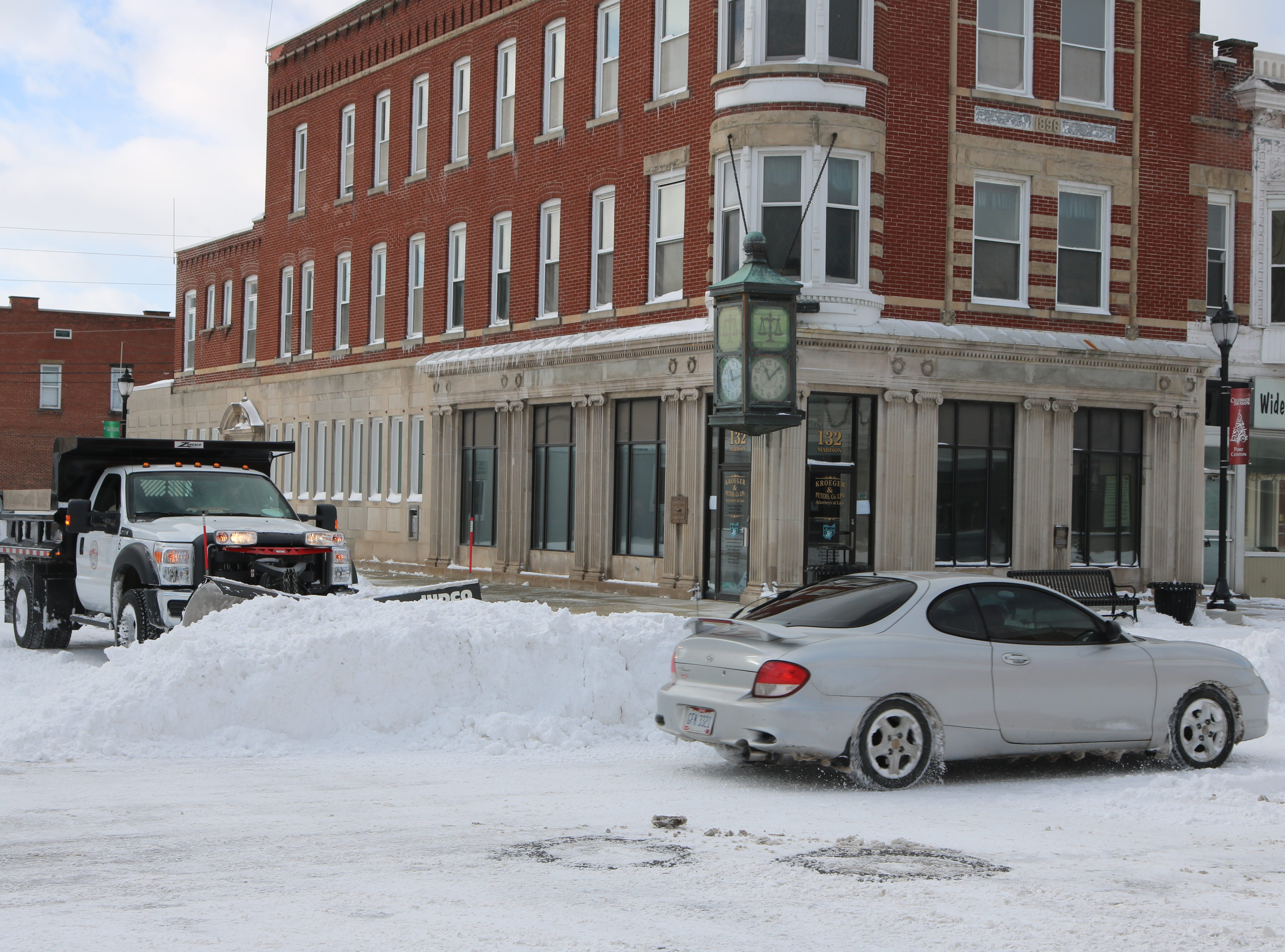 There was still plenty of snow on the roads Sunday, such as here in downtown Port Clinton, as crews continued to plow throughout the weekend.