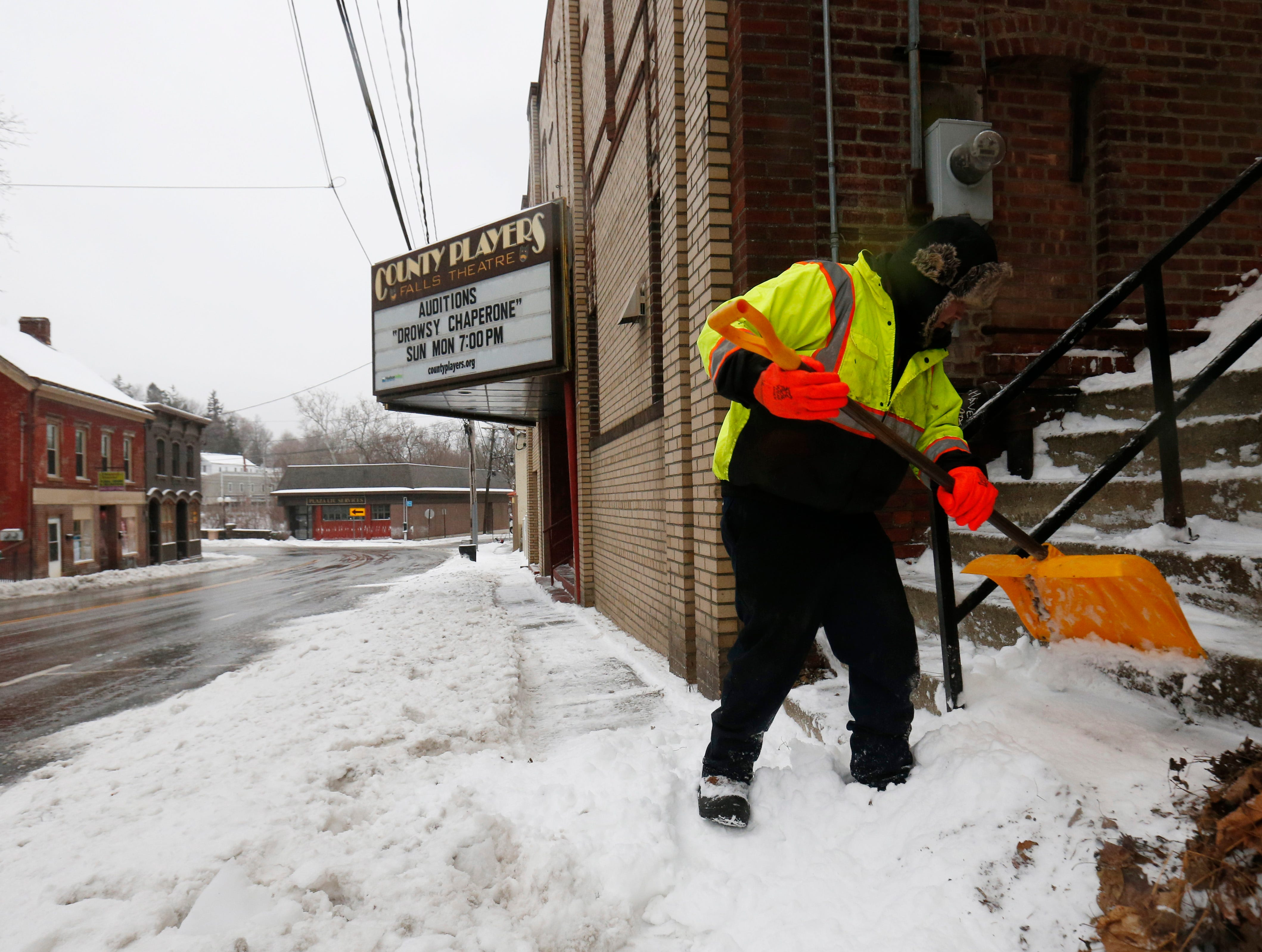 Christian Galindo clears steps leading to West Main Street in the Village of Wappingers Falls on January 20, 2019.