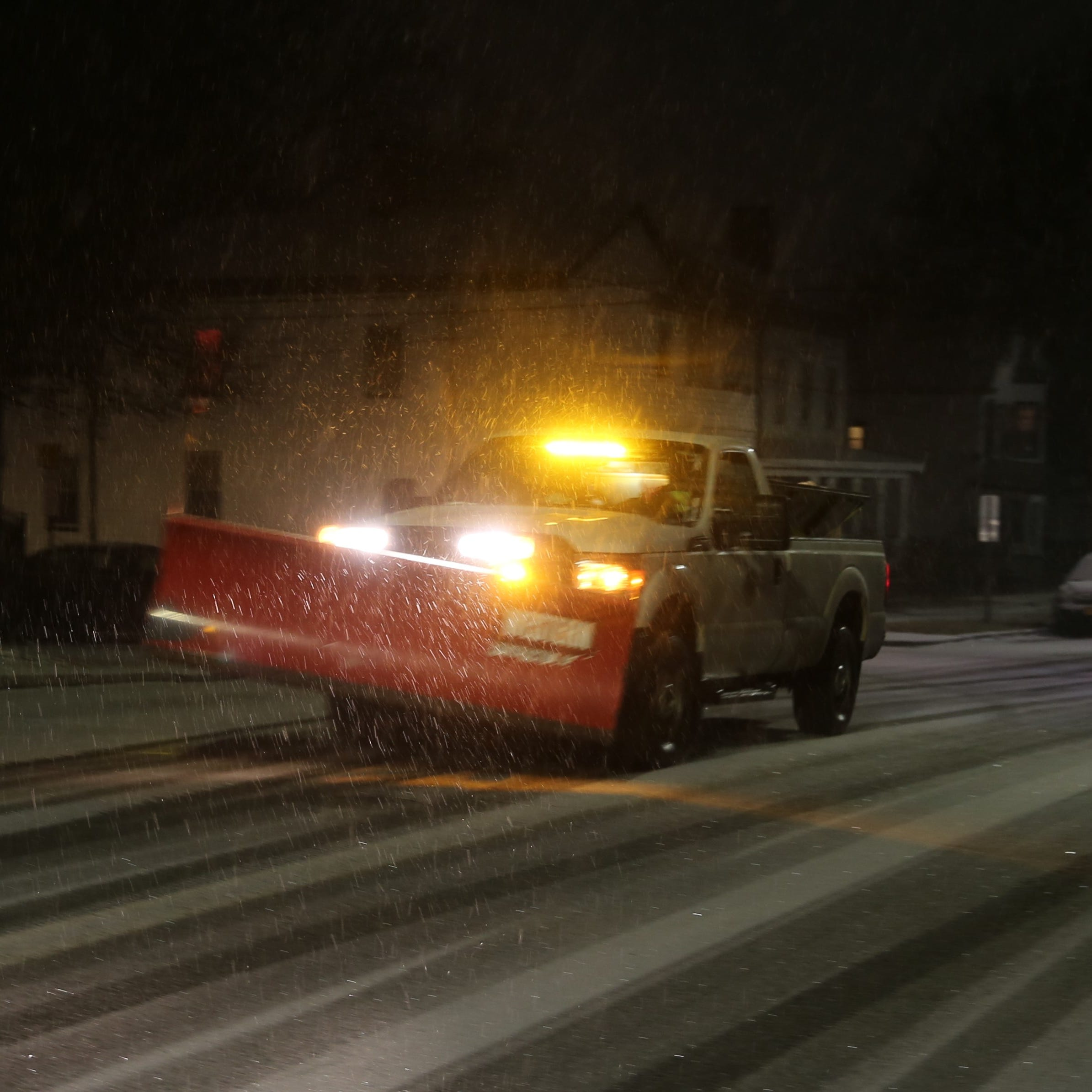A snow plow truck drives through the City of Poughkeepsie on Saturday night as snow begins to fall. The heaviest snow is expected to occur between 8 and 10 p.m. Saturday.
