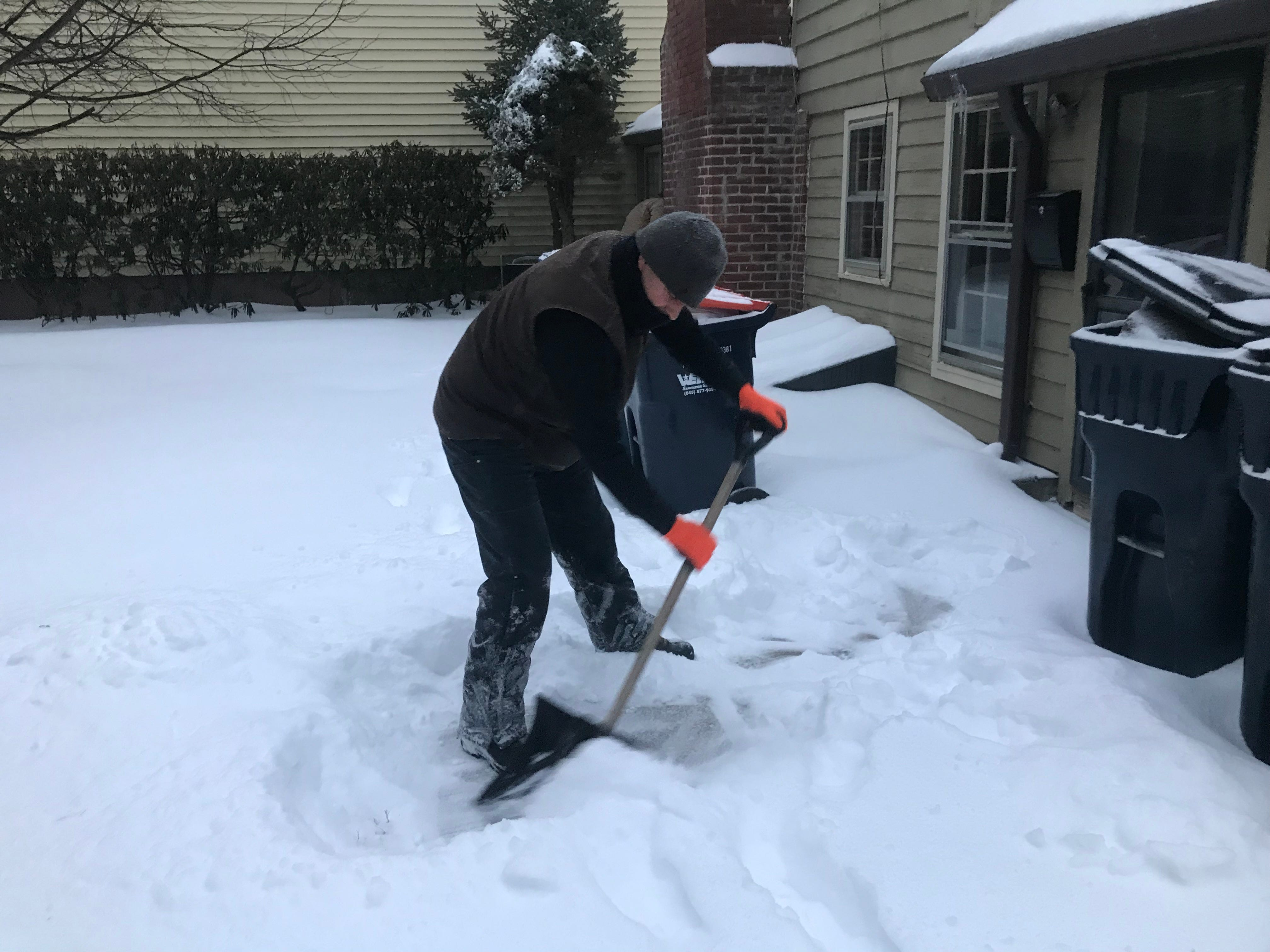 Aaron Murray of Red Hook, who works for J&K Curthoys in Rhinebeck, shovels snow in Rhinebeck Sunday morning.