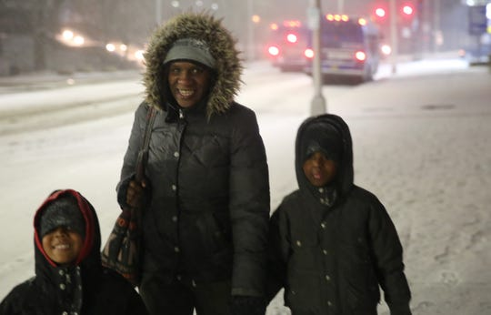 Jessica Hawley (middle), of the City of Poughkeepsie, walks home with her two sons, 7-year-old Tristan Hawley (right), and 5-year-old Julian Hawley (left), amid the snow on Saturday night. The two started an impromptu snowball fight in front of the Post Office.