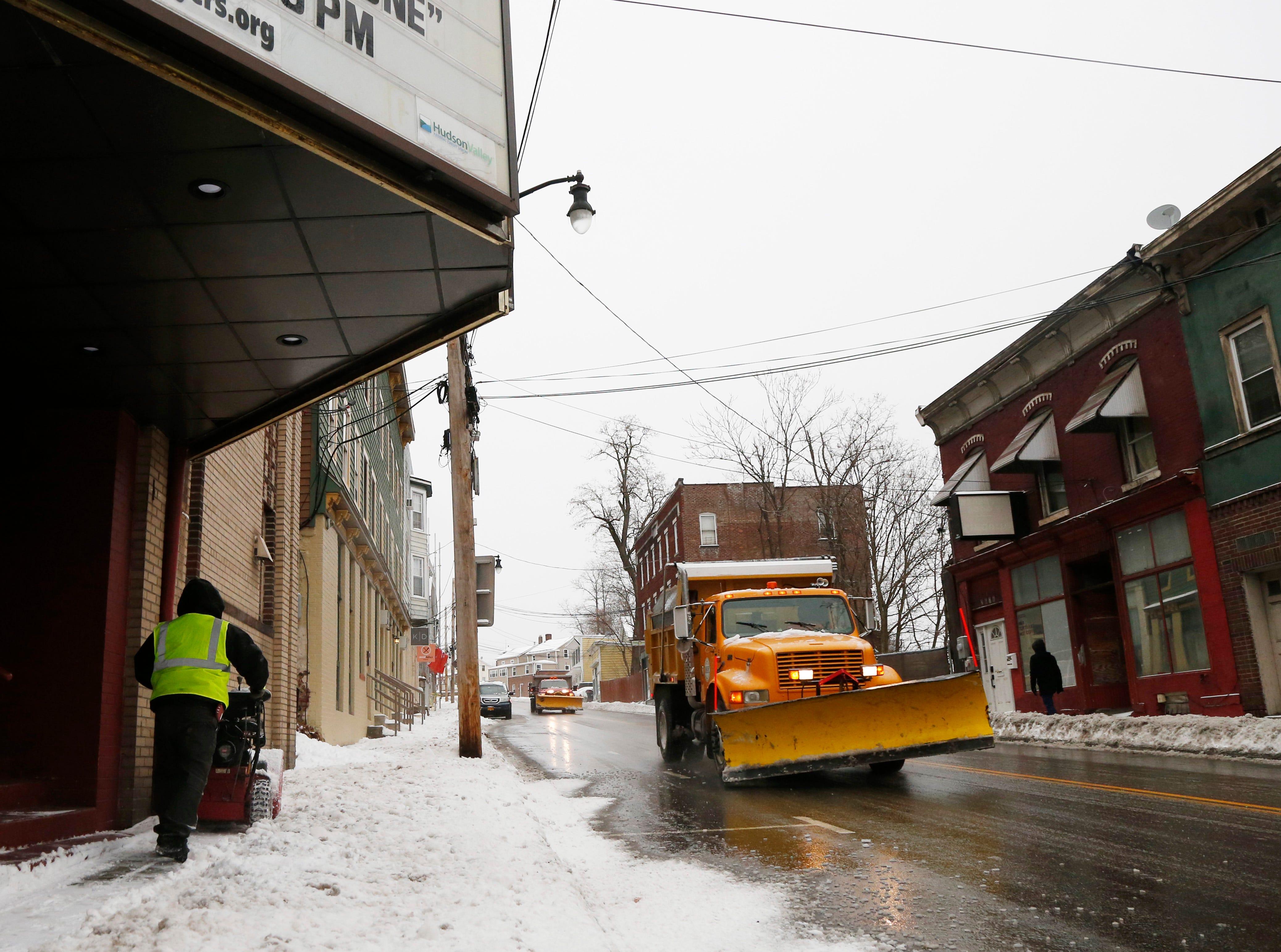 Mauricio Sibada clears the sidewalk along West Main Street as a Village of Wappingers Falls plow travels south in the Village of Wappingers Falls on January 20, 2019.