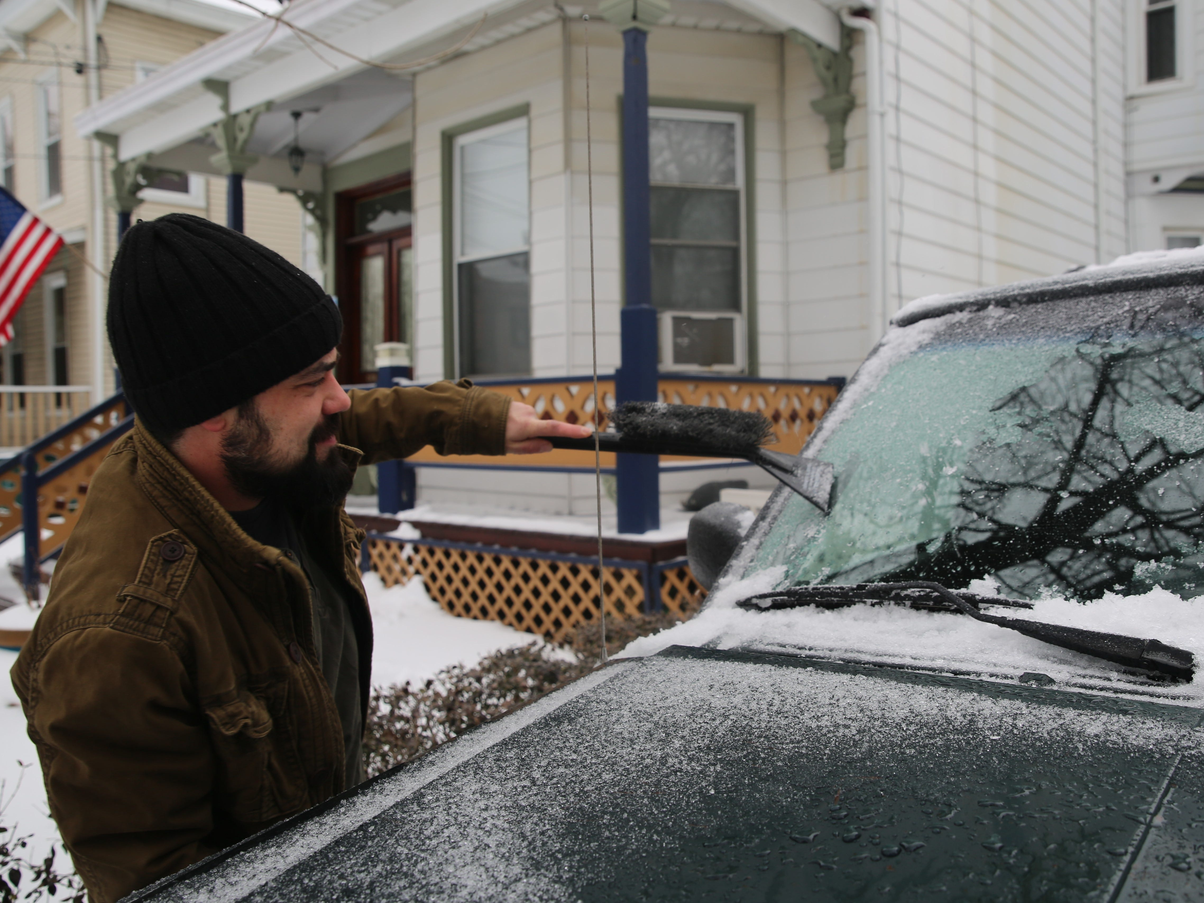 Jesse Tucker, 36, of the City of Poughkeepsie, works on getting the ice off of his Jeep on Sunday morning. Dutchess residents awoke to a combination of snow and ice that required some shoveling and scraping.