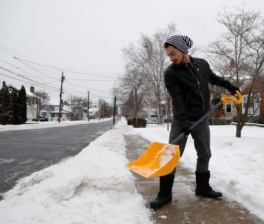 Jeffrey Boldrin Jr. clears snow from the sidewalk on Mesier Avenue in the Village of Wappingers Falls on January 20, 2019.