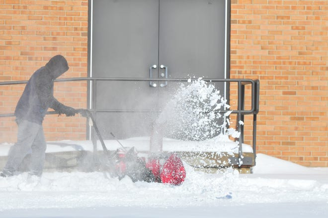 Sidewalks are cleared with a snowblower Sunday afternoon at Charles Elementary School.