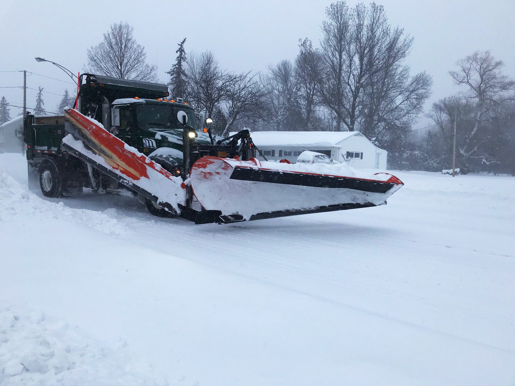A plow heads east on Elmwood in Brighton Sunday morning.
