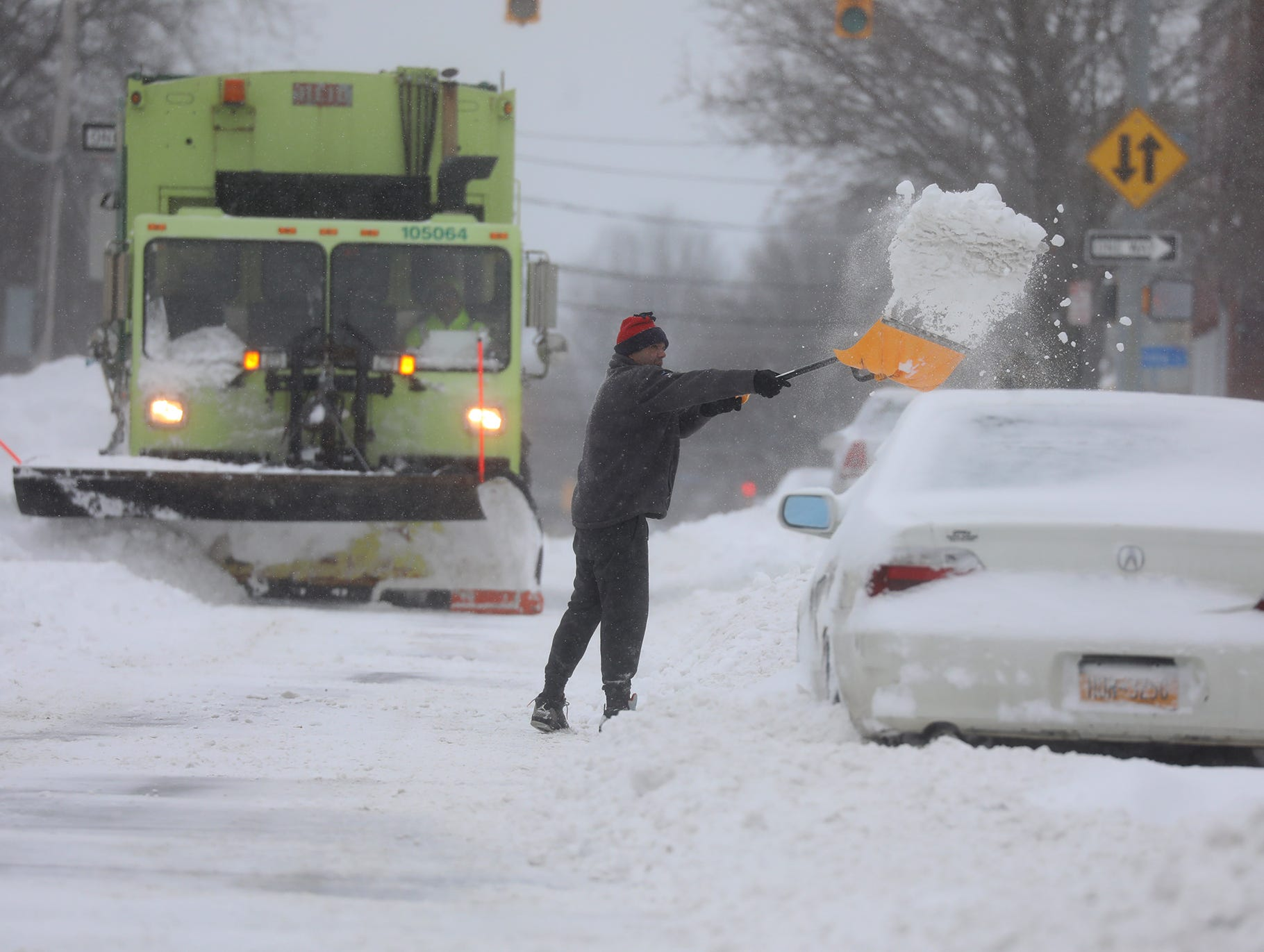 Over a foot of snow fell overnight, with advisories issued about unnecessary travel and cold temperatures.  Many people heeded the warnings and stayed home, Sunday, Jan. 20, 2019.  Benjamin Diaz shovels from his driveway on Smith Street as a plow comes down his street.