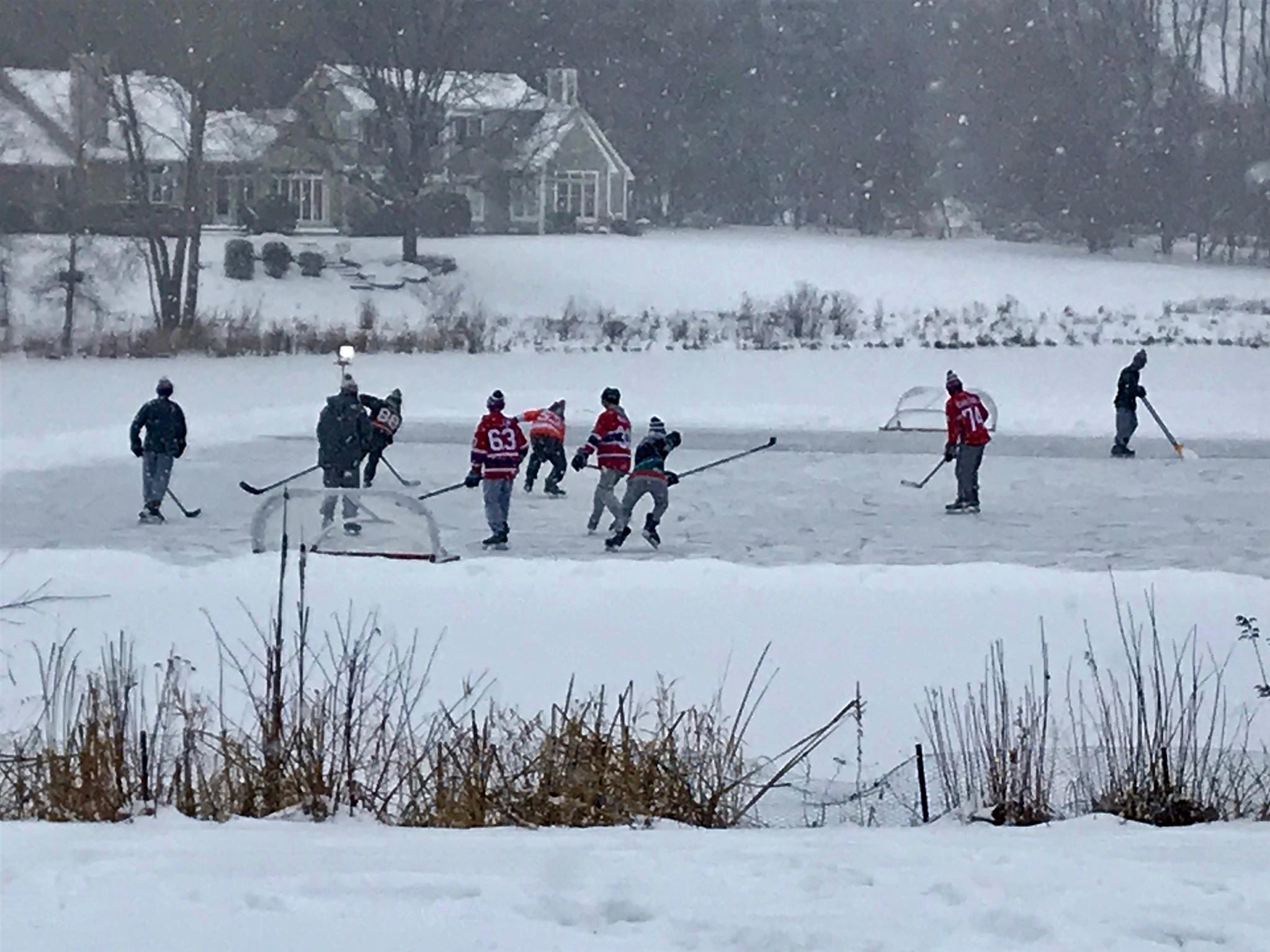 "A Webster neighborhood plays a pickup hockey game during a snow storm on Jan. 19, 2018. ""It's a perfect representation of why winters in Rochester are actually beautiful,"" said Greg Kennedy of Webster."