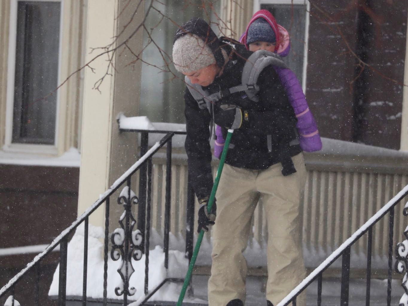 Carin LeFevre sweeps the stairs of her Monroe Avenue home with her daughter, Cora McCormick, on her back.