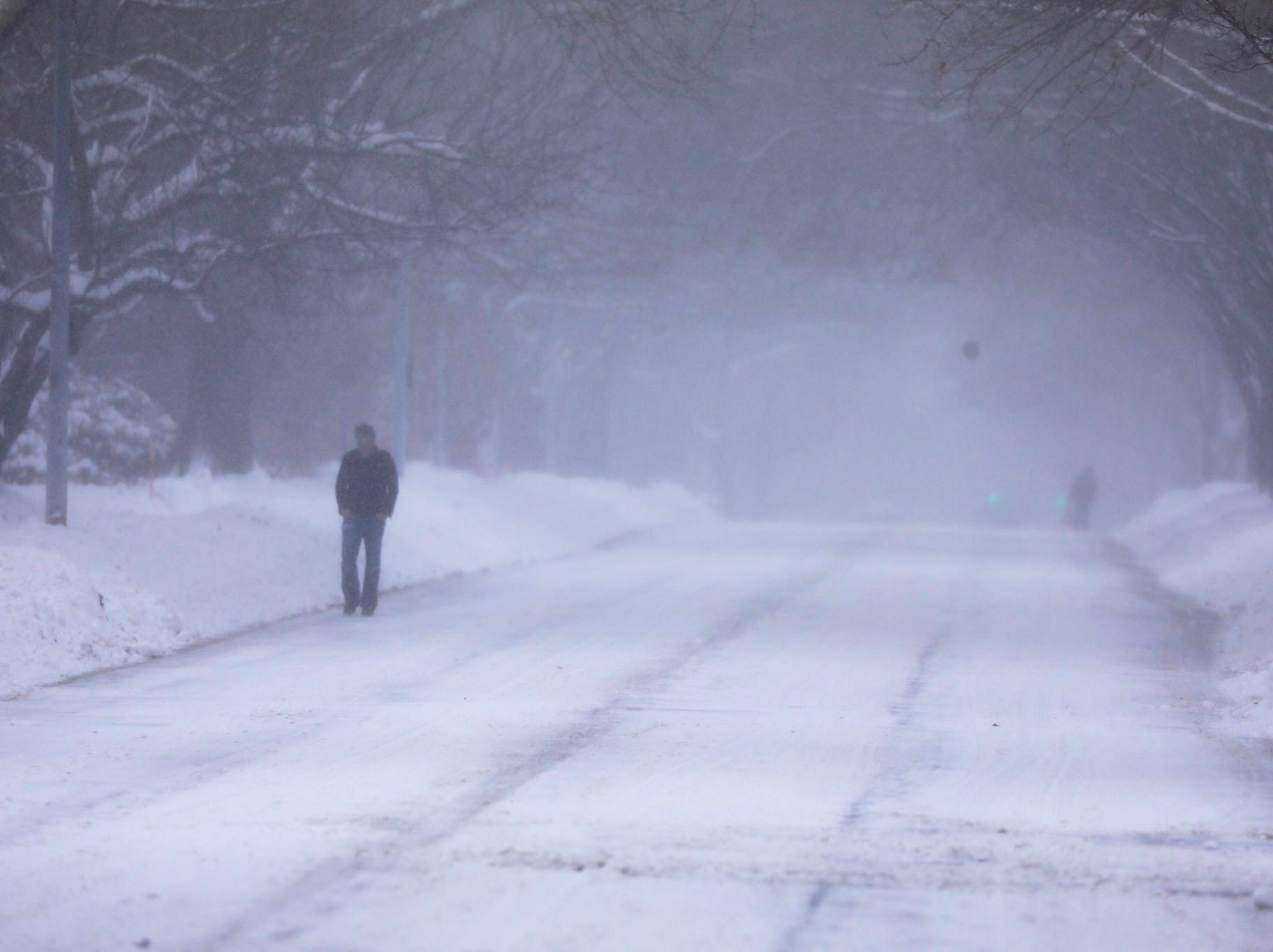 Pedestrians walk on the street on East Avenue as the snow continues to fall Sunday morning.