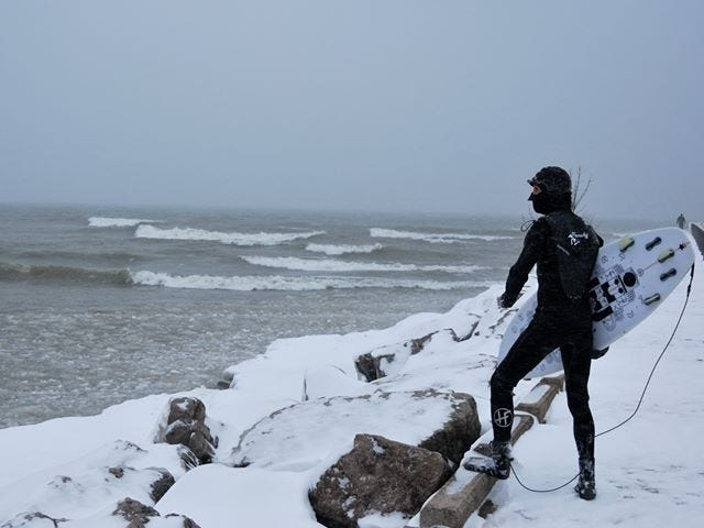 Aurelien Bouche-Pillon gets ready to surf on Lake Ontario during a snowstorm on Jan. 19, 2018.