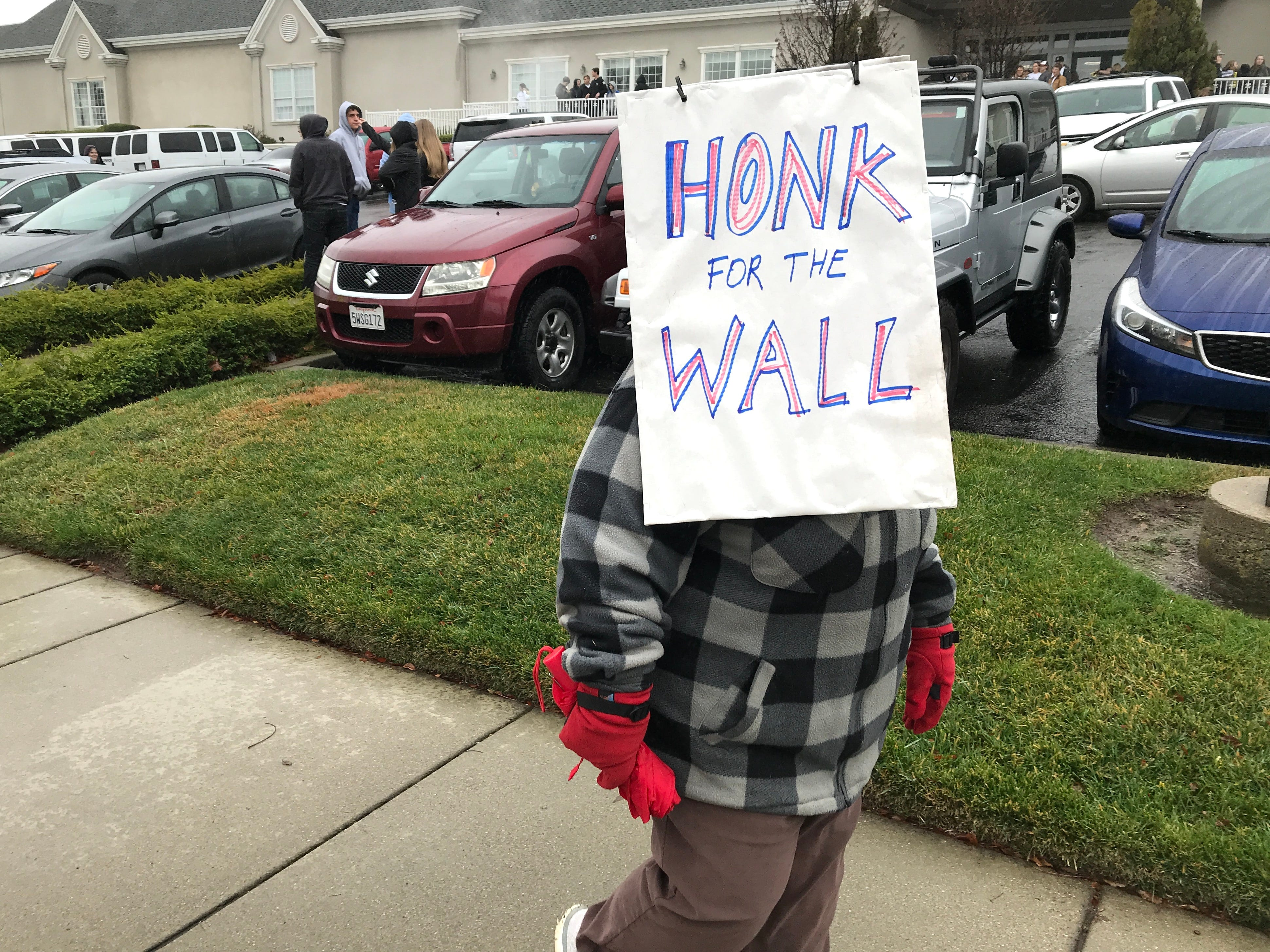 Sheila Hayes of Redding used her sign to shield herself from the rain at the Build That Wall! rally in Redding on Saturday.