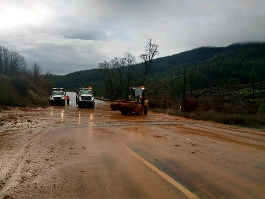 A Caltrans crew clears mud and debris from Highway 299 west of Weaverville on Sunday.