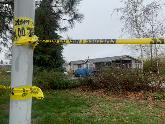 Caution tape outlines a property following a quadruple murder and the suspect shot and killed by deputies on Saturday night.