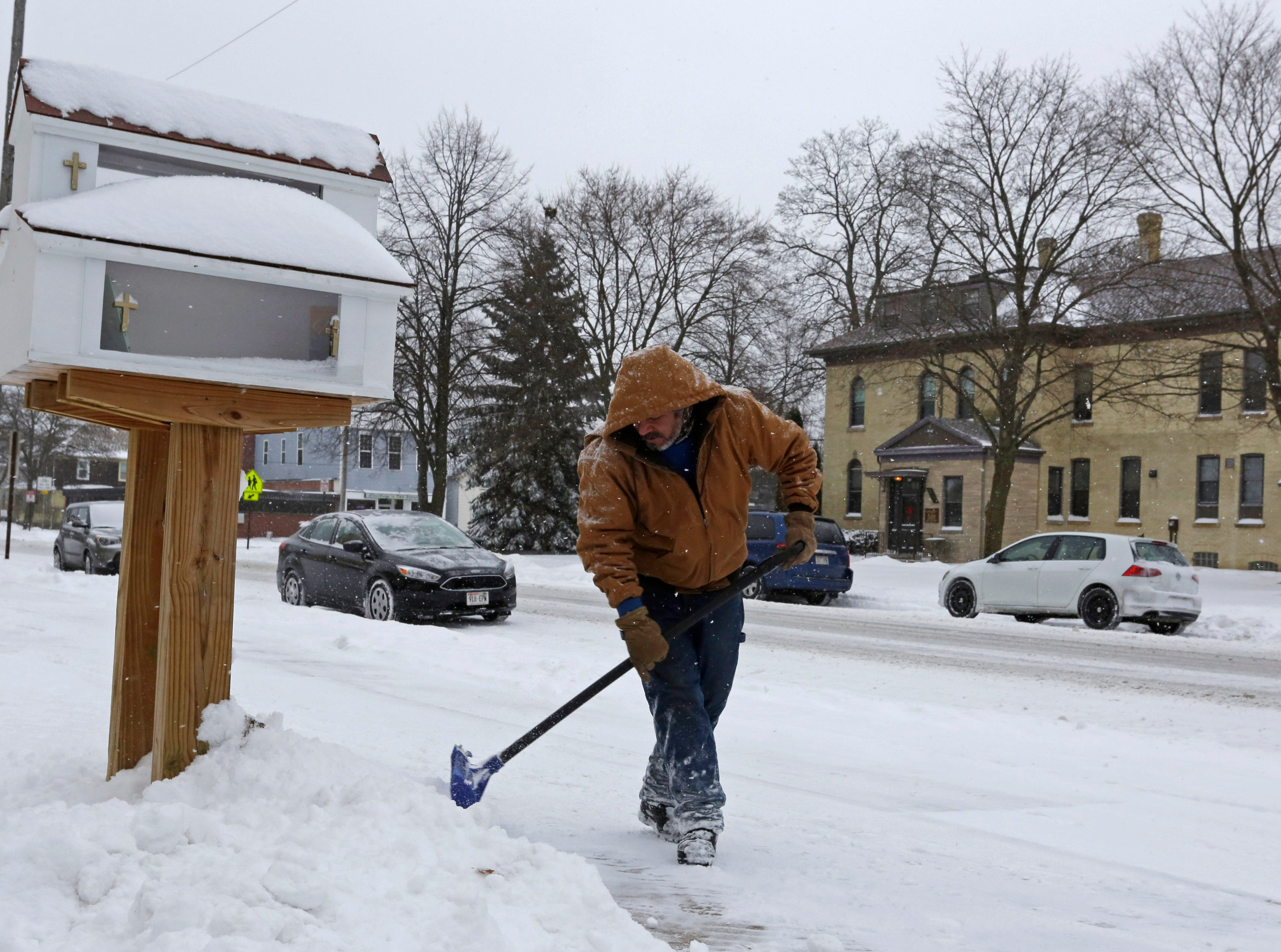 Pedro Astralop shoves snow near Holy Name, Saturday, January 19, 2019, in Sheboygan, Wis.