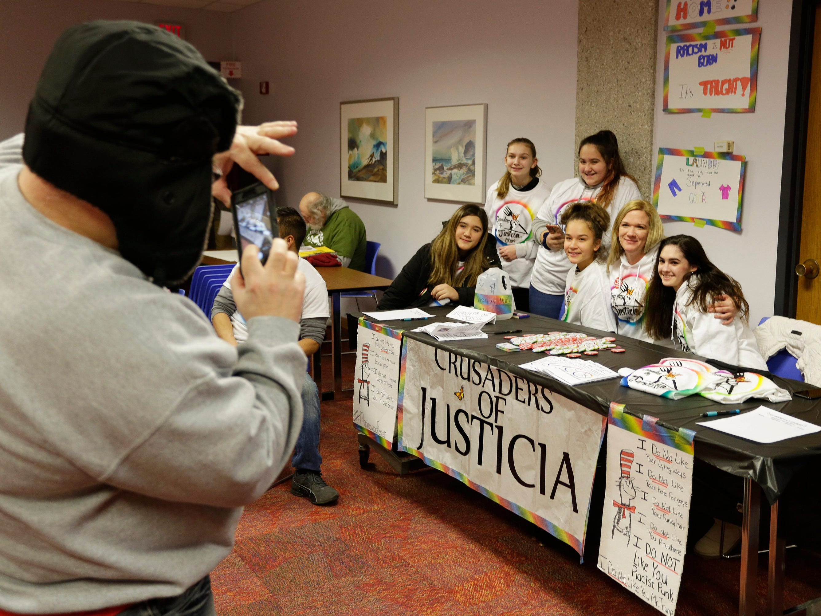 Bryan Pfeiffer takes a photo of Crusaders of Justice at Mead Public Library, Saturday, January 19, 2019, in Sheboygan, Wis. The Manitowoc based group focuses on immigration issues.